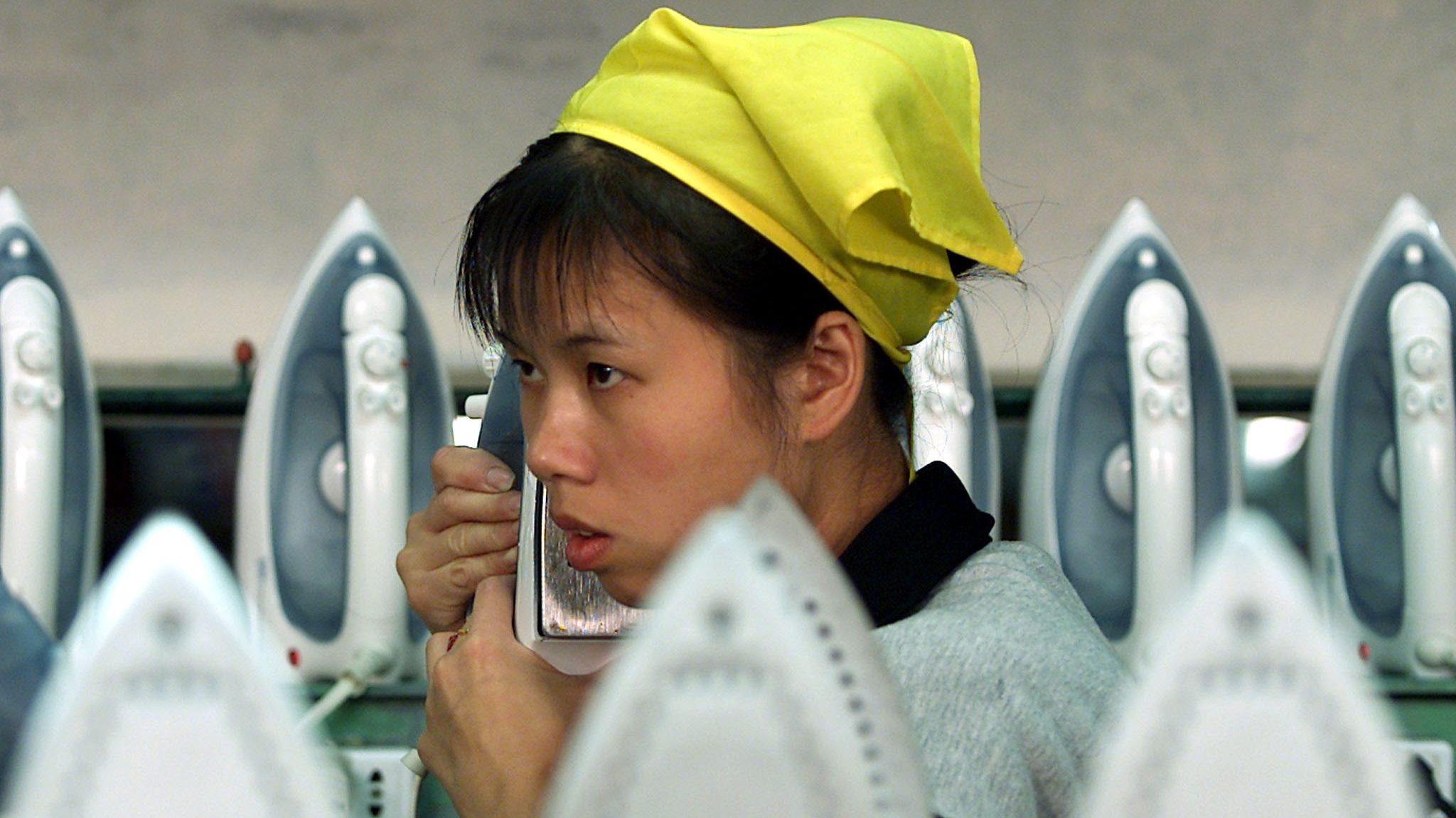 A mainland Chinese worker checks an iron between assembly lines at a household appliances factory established by Taiwanese in Xiamen, Fijian province which enjoys a close trade and investment ties with Taiwan, November 26, 2001. Most Taiwanese believe closer economic integration with the mainland is an irreversible trend.