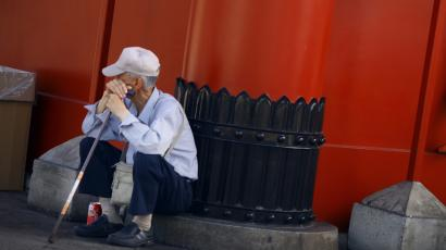 A boy clings to the wall of a temple gate as an elderly man sits nearby in Tokyo, Wednesday, Aug. 11, 2010. (AP Photo/Junji Kurokawa
