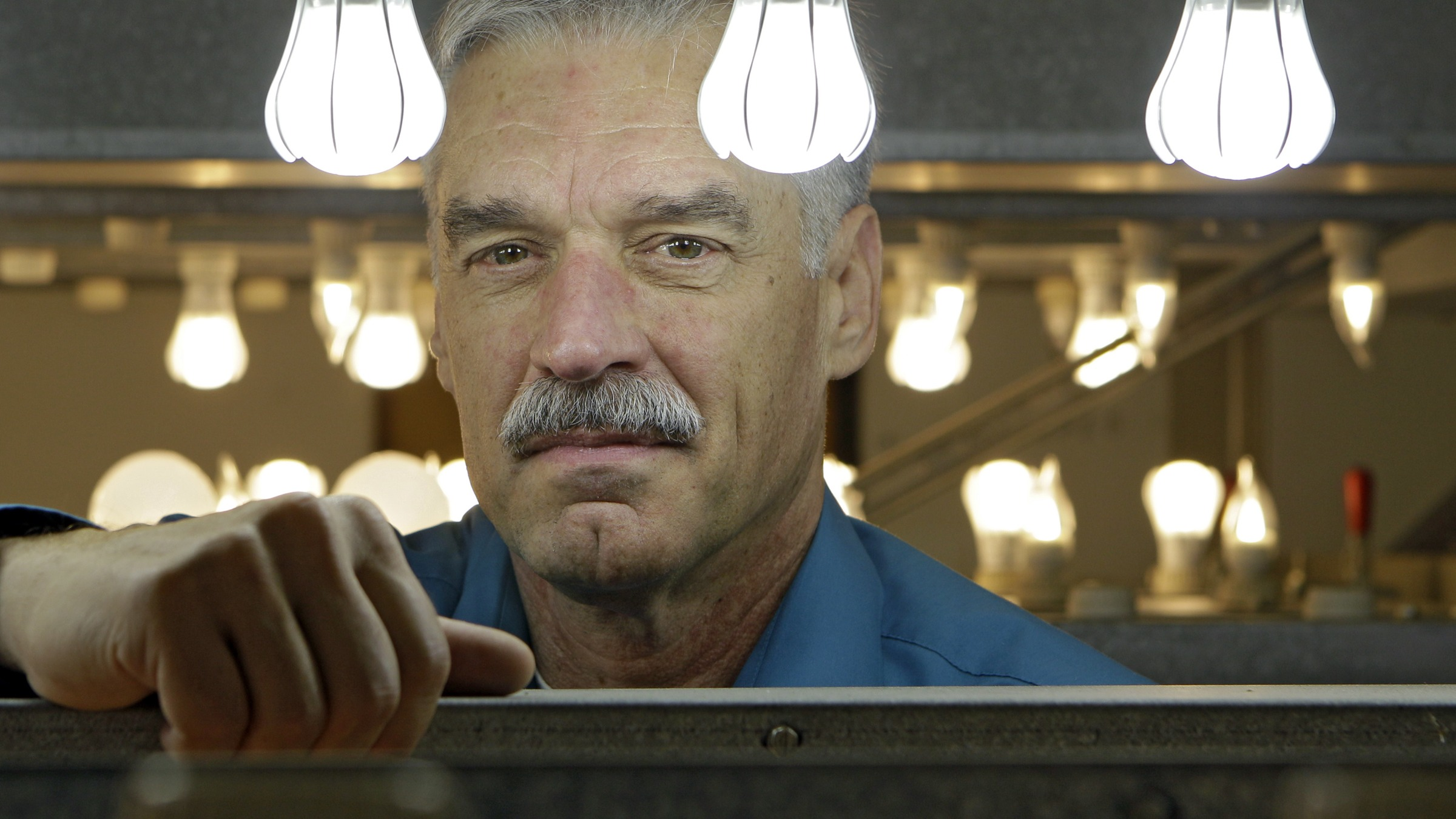Gary Allen, lead inventor for the General Electric 9-watt Energy Smart® LED light bulb, poses with some of his creations during aging tests at the lighting group's Nela Park headquarters in East Cleveland, Ohio Wednesday, Oct. 19, 2011. (AP Photo/Mark Duncan)
