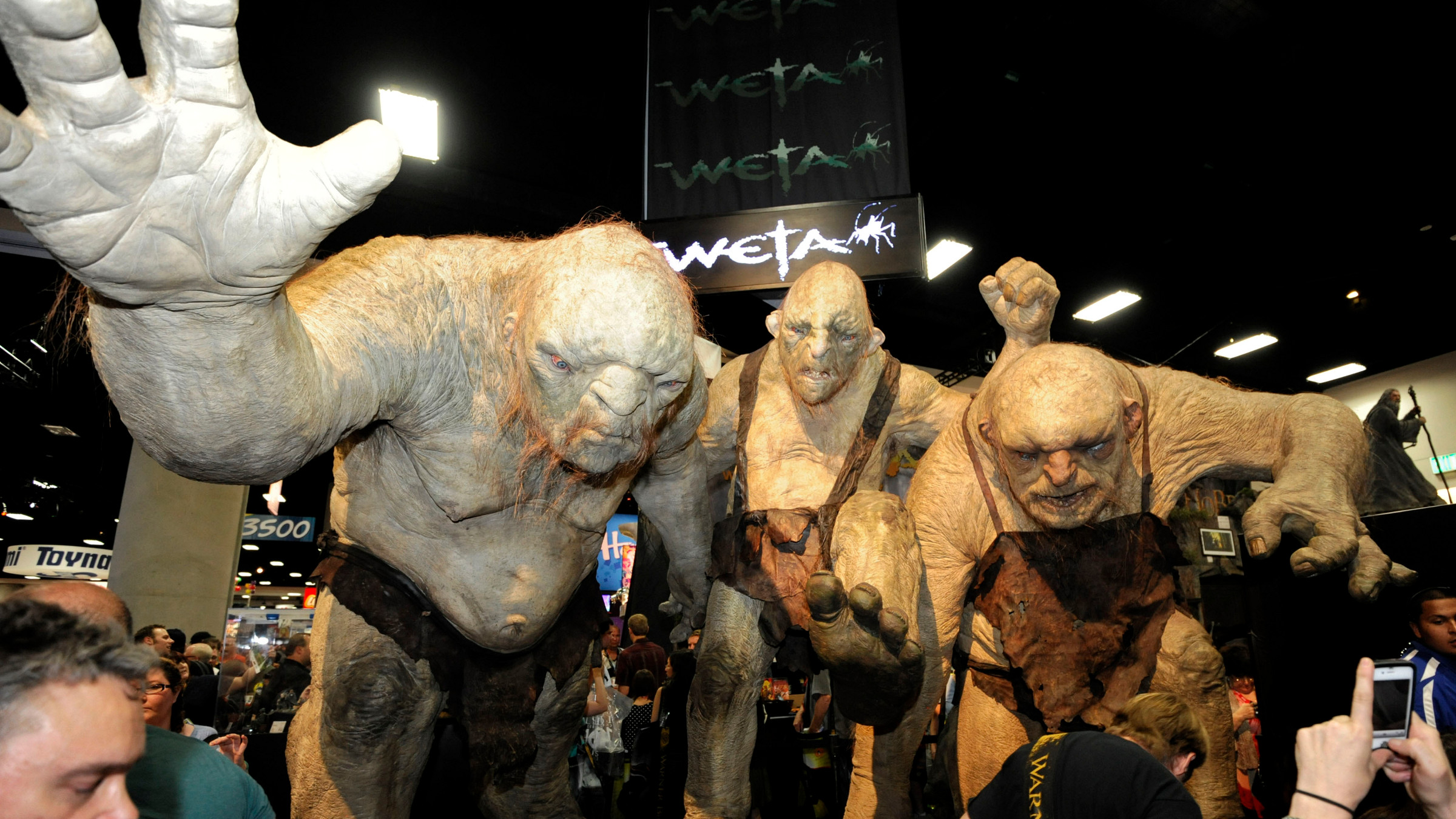 Fans walk past huge Stone Troll figures from the Lord of the Rings at the Comic-Con preview night held at the San Diego Convention Center on Wednesday July 11, 2012, in San Diego.