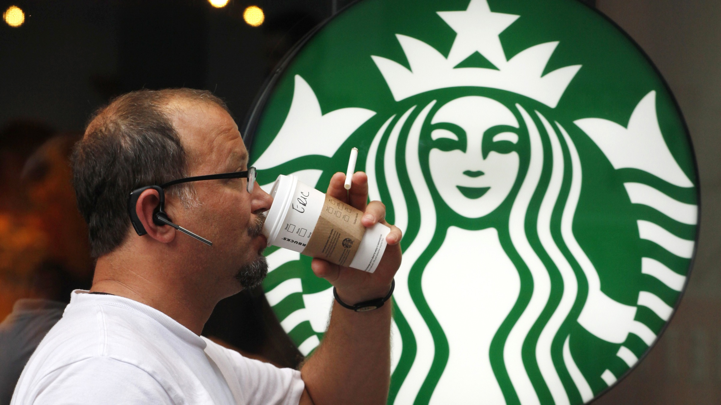 In this July 11, 2013 photo, a man drinks a Starbucks coffee in New York. (AP Photo/Mark Lennihan)