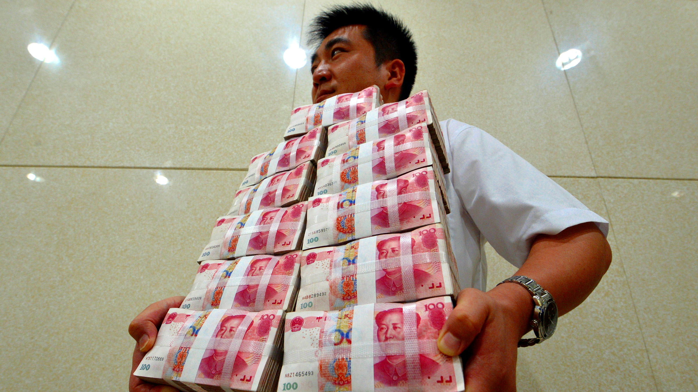 An employee carries bundles of 100 yuan Chinese bank notes to store after counting at a bank in Taiyuan, Shanxi province July 4, 2013. Chinese authorities allowed short-term borrowing costs to spike to record levels on June 20, sending a blunt but effective message to banks that it was determined to bring risky credit growth under control. The crackdown, however, has only increased China Inc's reliance on shadow banking and its various components, underscoring the system's importance as China's rigid financial industry maneuvers through an economic slowdown.