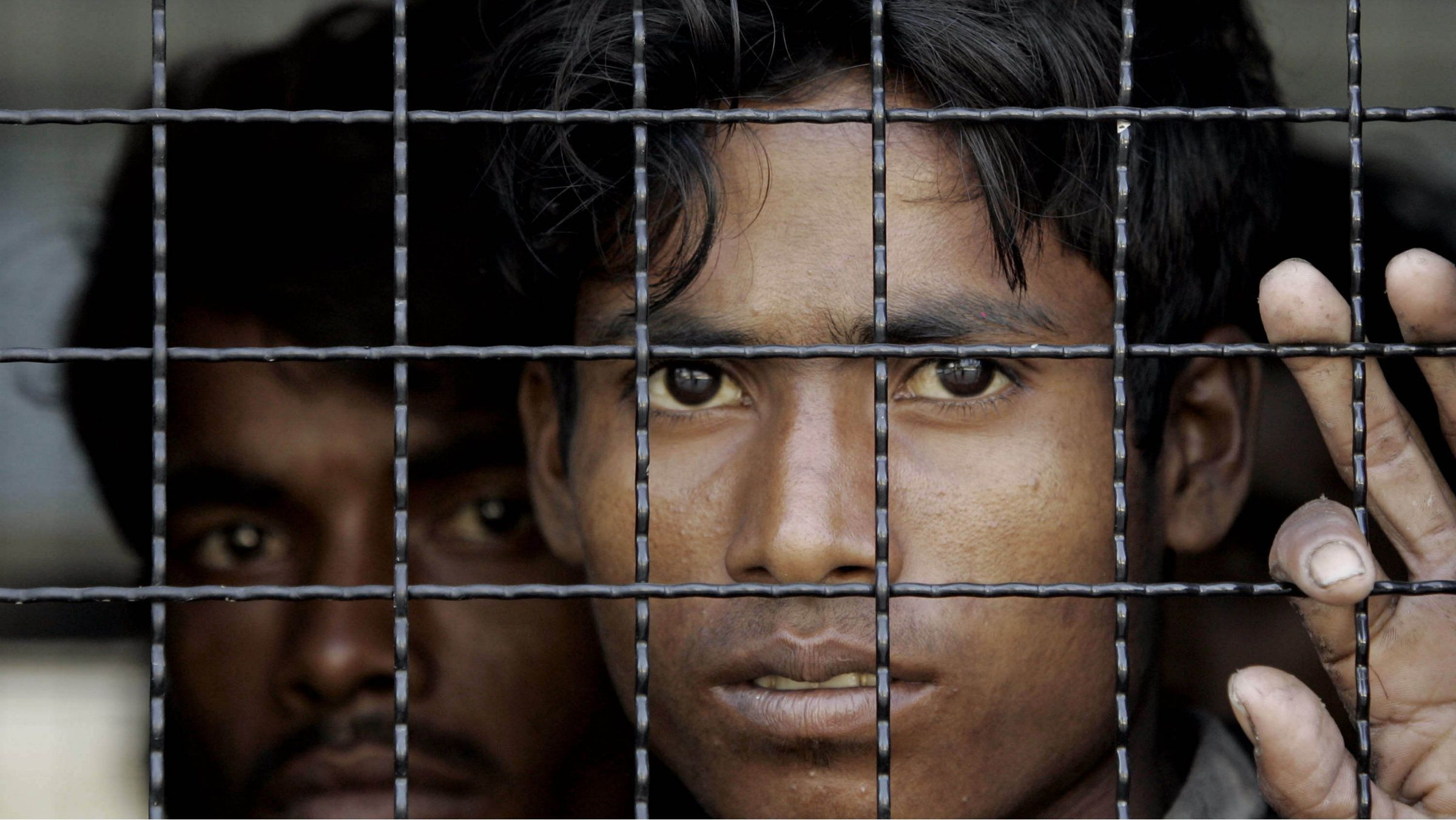 Rohingya migrants look out from the window of a Thai police van in 2009.