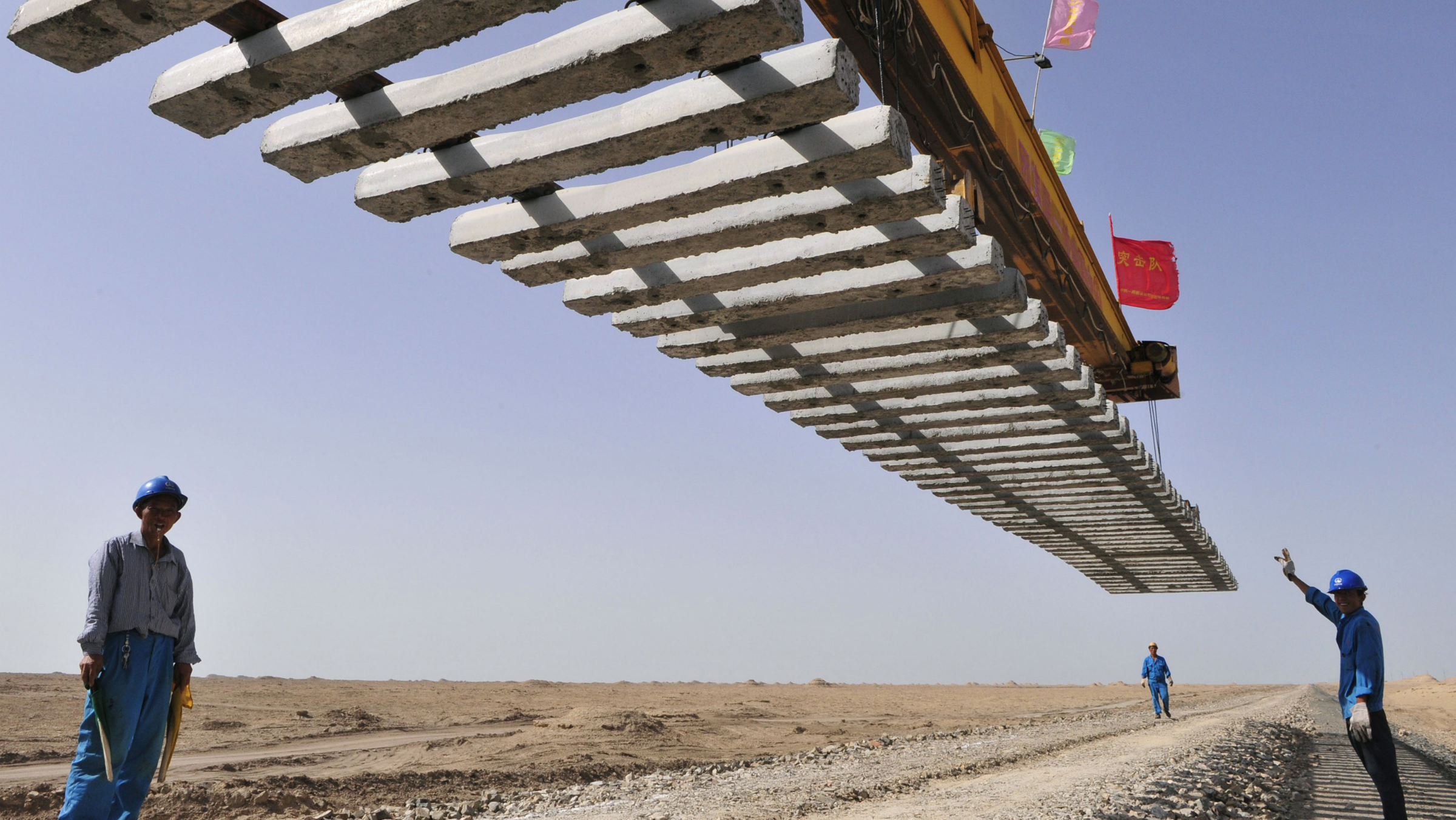 Workers direct a crane to lay a segment of tracks on the Kumul-Lop Nor line's railway bed in Lop Nor, Xinjiang Uighur Autonomous Region July 15, 2012. The line, which is the first going to Lop Nor, is estimated to be completed on July 20, 2012, local media reported. Picture taken July 15, 2012. REUTERS/Rooney Chen