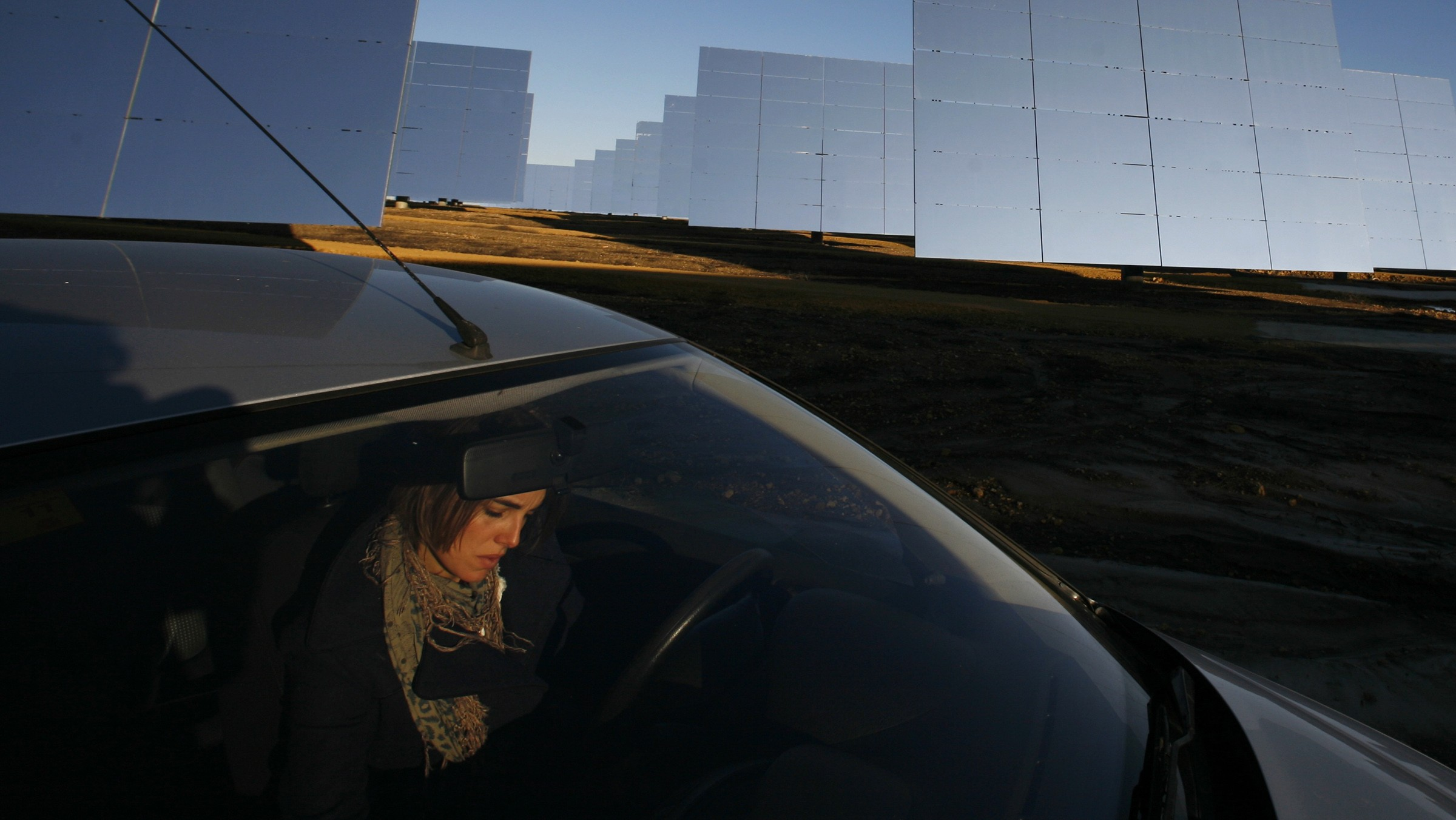 "A woman sits in a car in the PS20 solar plant at ""Solucar"" solar park in Sanlucar La Mayor, near Seville, January 8, 2010. The solar thermal power plant uses mirrors to concentrate the sun's rays onto towers where they produce steam to drive a turbine, producing electricity. REUTERS/Marcelo del Pozo (SPAIN - Tags: ENERGY ENVIRONMENT BUSINESS SOCIETY) - RTR28NUG"