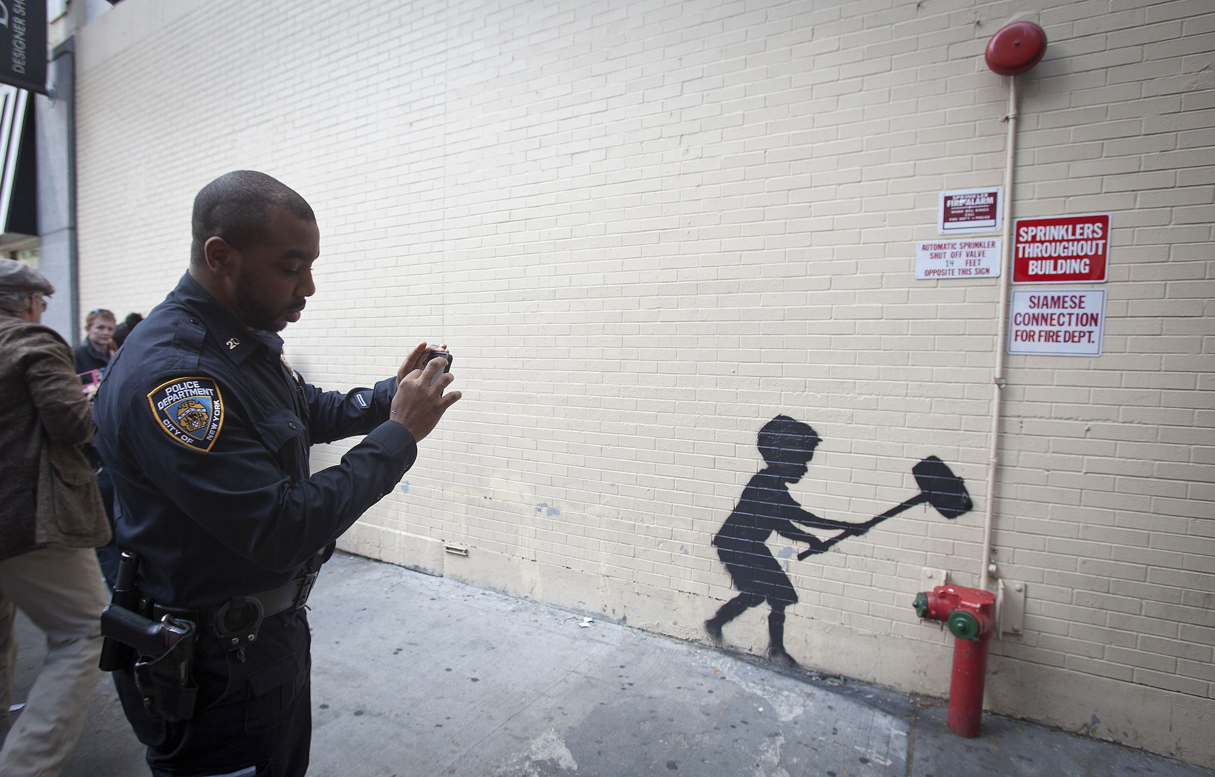 """A police officer takes a photo of a new installation of British graffiti artist Banksy's art in New York, October 20, 2013. According to local media, Banksy has caught the attention of New York mayor Michael Bloomberg who said, """"It's a sign of decay and loss of control"""" and that graffiti ruins property.  REUTERS/Carlo Allegri (UNITED STATES - Tags: SOCIETY) - RTX14I51"""