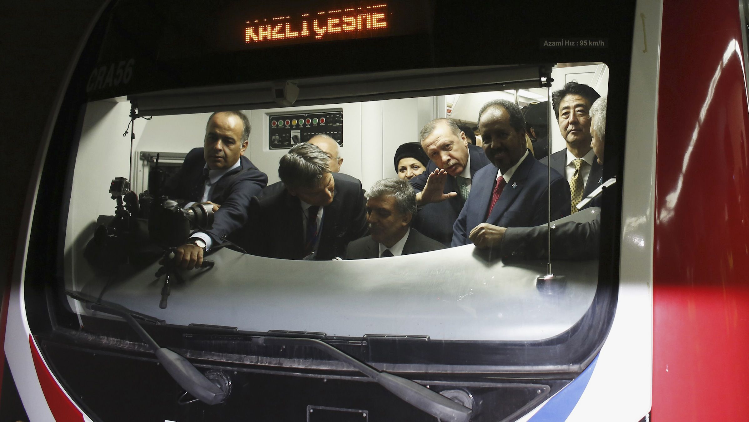 Japanese Prime Minister Shinzo Abe (R), Turkey's Prime Minister Tayyip Erdogan (3rd R) and President of Somalia Hassan Sheikh Mohamud (2nd R) stand around Turkey's President Abdullah Gul (seated) as he rides the ceremonial service of a train during the opening ceremony of Marmaray, a subway links Europe with Asia some 60 metres below the Bosphorus Strait, in Istanbul October 29, 2013. Turkey opened the world's first underwater rail link between two continents on Tuesday, connecting Asia and Europe and allowing PM Erdogan to realise a project dreamt up by Ottoman sultans more than a century ago.   REUTERS/Murad Sezer (TURKEY - Tags: POLITICS TRANSPORT BUSINESS TPX IMAGES OF THE DAY) - RTX14SU1