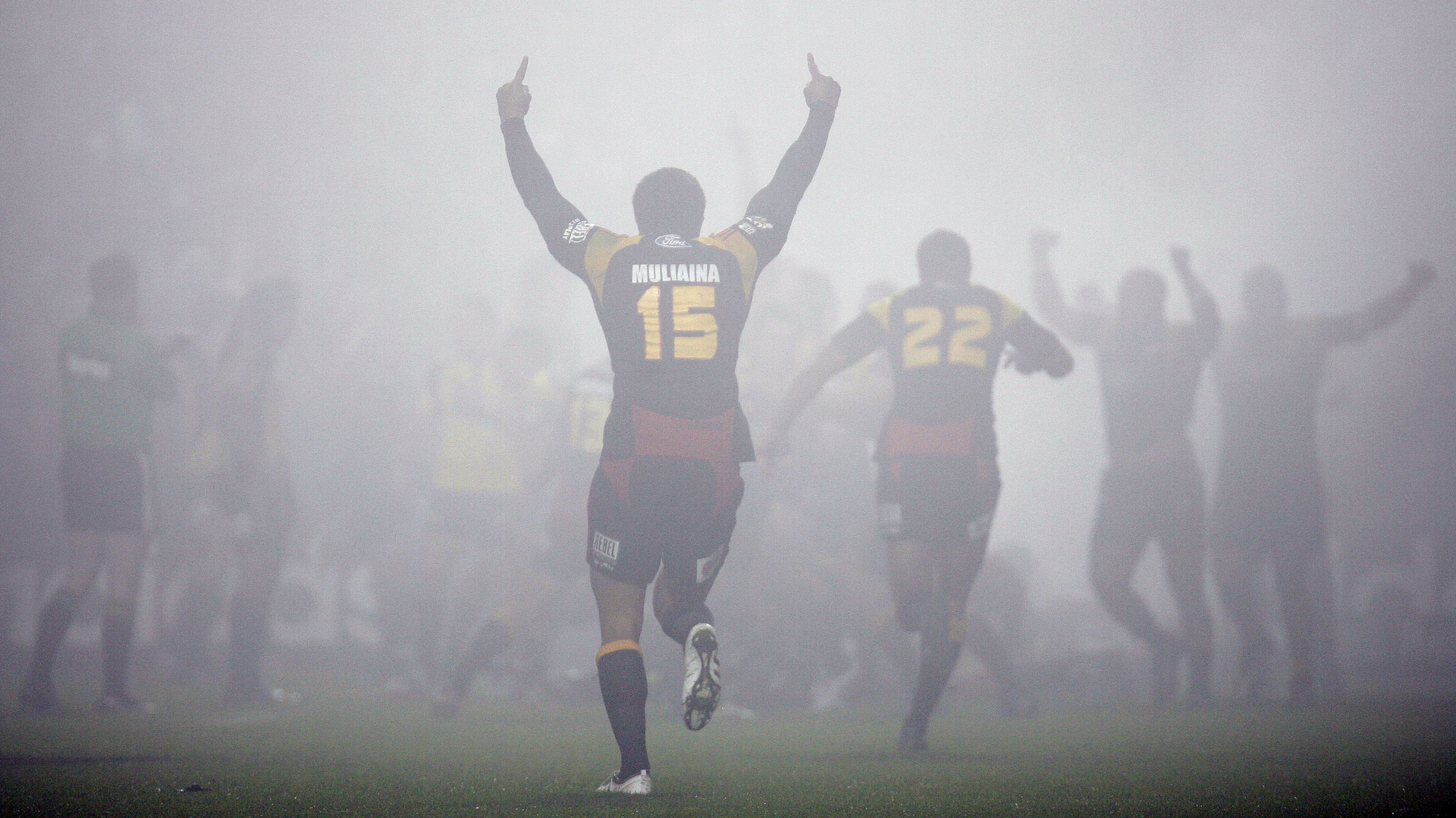 Mils Muliaina (C), captain of New Zealand's Waikato Chiefs, celebrates as he runs towards his team mates after beating New Zealand's Wellington Hurricanes during a foggy day at the Super 14 semi-final rugby match at Waikato Stadium in Hamilton, May 22, 2009. REUTERS/Nigel Marple