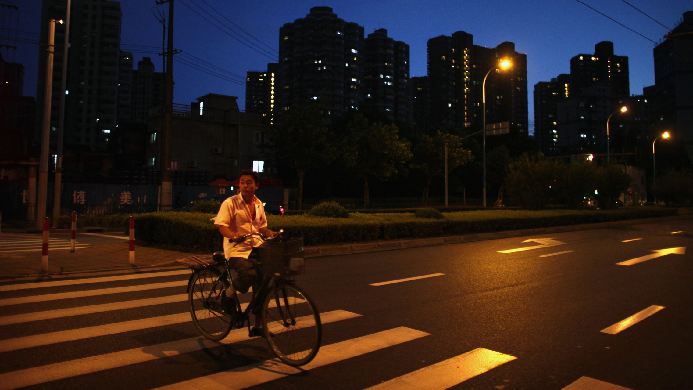 A man rides his bicycle at a residential area in downtown Shanghai August 24, 2012. China is studying new tightening measures to strengthen controls on the property market, the official Xinhua news agency said late on Thursday, citing the Ministry of Housing and Urban-Rural Development. REUTERS/Carlos Barria