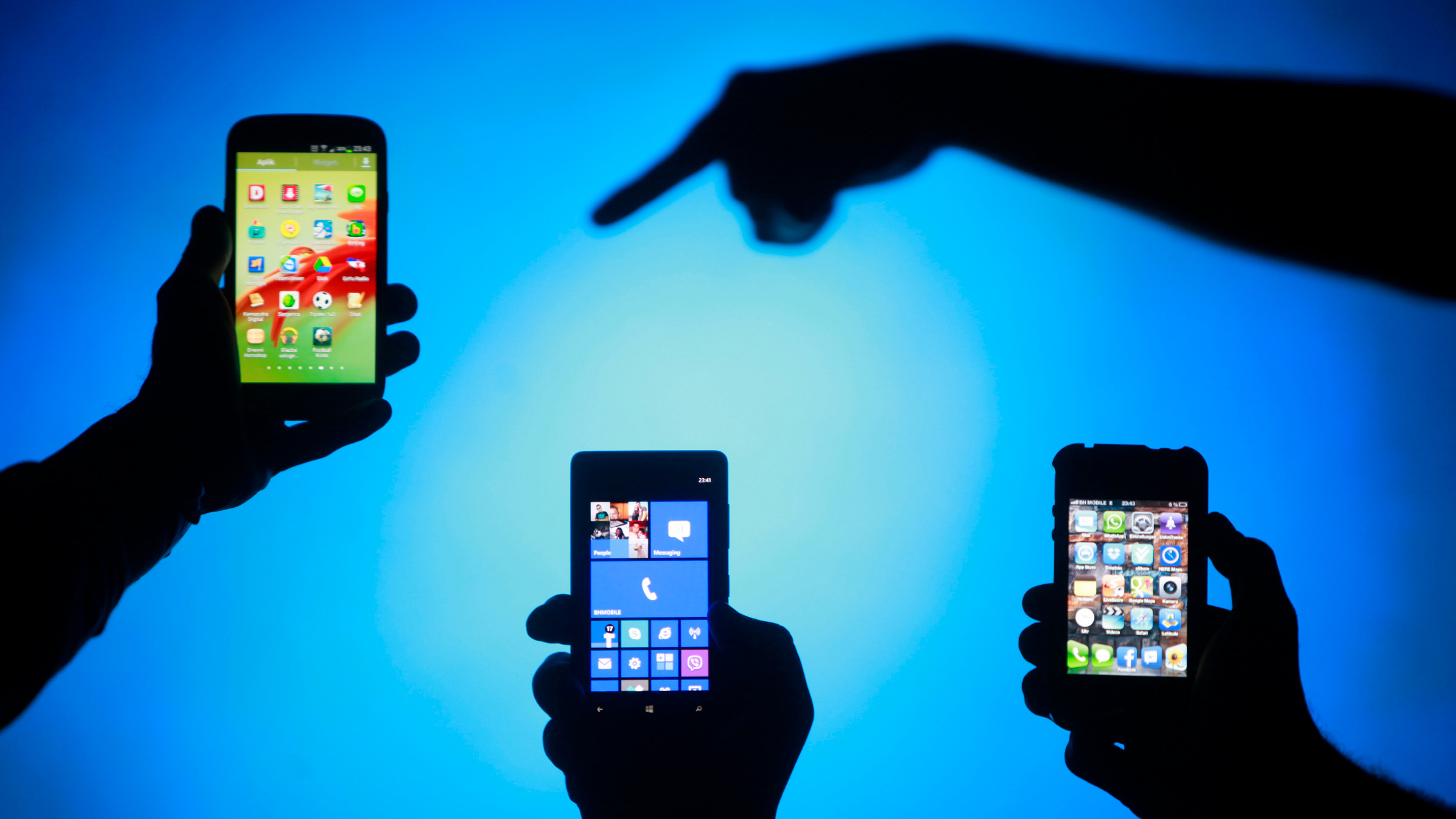 Men are silhouetted against a video screen as they pose with Samsung Galaxy S3, Nokia Lumia 820 and iPhone 4 smartphones (L-R) in this photo illustration taken in the central Bosnian town of Zenica, May 17, 2013.