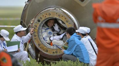 Chinese astronaut Nie Haisheng waves before getting out of the re-entry capsule of China's Shenzhou-10 spacecraft after it landed at its main landing site in Inner Mongolia Autonomous Region, June 26, 2013. Three Chinese astronauts returned to Earth on Wednesday, touching down in north China's Inner Mongolia after a successful 15-day mission in which they docked with a manned space laboratory. REUTERS/China Daily