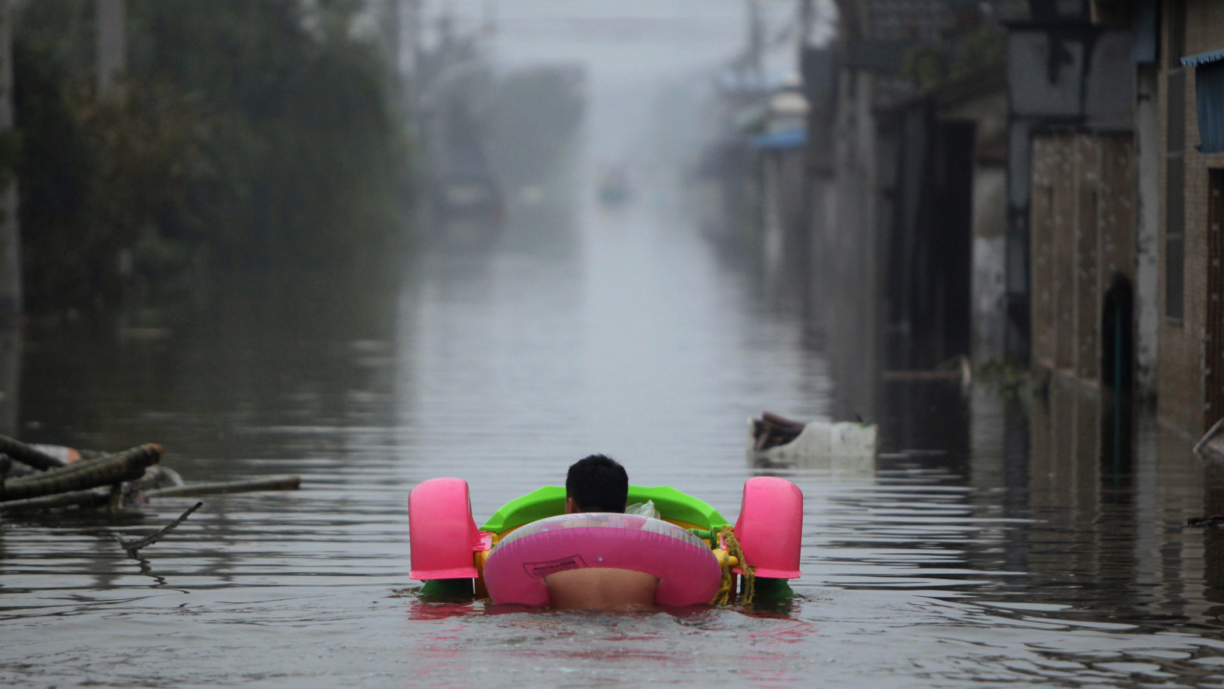 A man pushes a toy boat as he wades down a flooded street with a lifebuoy after Typhoon Fitow hit Tongguang village of Yuyao, Zhejiang province October 9, 2013. Heavy downpours hit Zhejiang and Fujian provinces after Typhoon Fitow made landfall in China on Monday, inundating roads and houses, and causing river breaches and power failures. Over 70 percent of the downtown area of the worst-hit Yuyao city has been flooded though no casualties have been reported so far, Xinhua News Agency reported. Picture taken October 9, 2013. REUTERS/China Daily