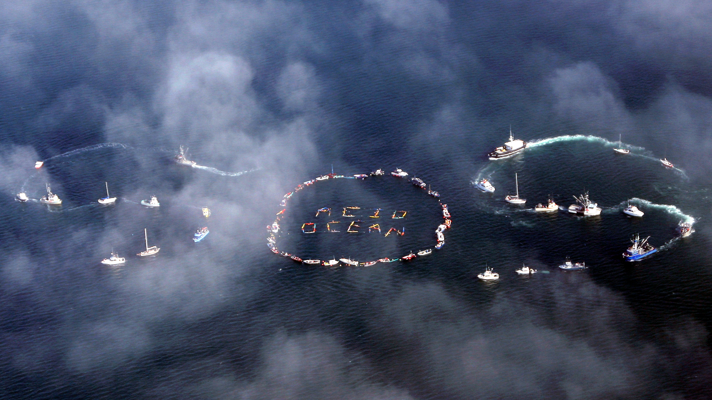 """Commercial fishermen and other mariners form the word """"SOS"""" during an event held to spread the message of saving the oceans from acidification caused by fossil fuel emissions, in Homer, Alaska, September 6, 2009. Over a hundred boats and hundreds of members of the fishing community participated in the event."""