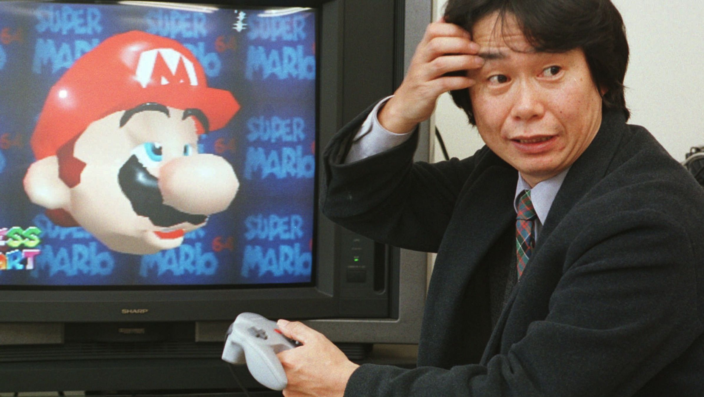"""ADVANCE FOR JAPAN-PROFILE-NINTENDO INVENTOR STORY--Shigeru Miyamoto, creator of Super Mario video game series, scratches eyebrow as he operates his latest blockbuster product, Super Mario 64, in his office at the Nintendo Co. headquarters in Kyoto, southwest of Japan, Feb. 6, 1997.   """"I'm so glad I work for a toy-maker,"""" Miyamoto, 44, said with a smile. """"I view the company as a patron and sponsor.""""   (AP Photo/Atsushi Tsukada)"""