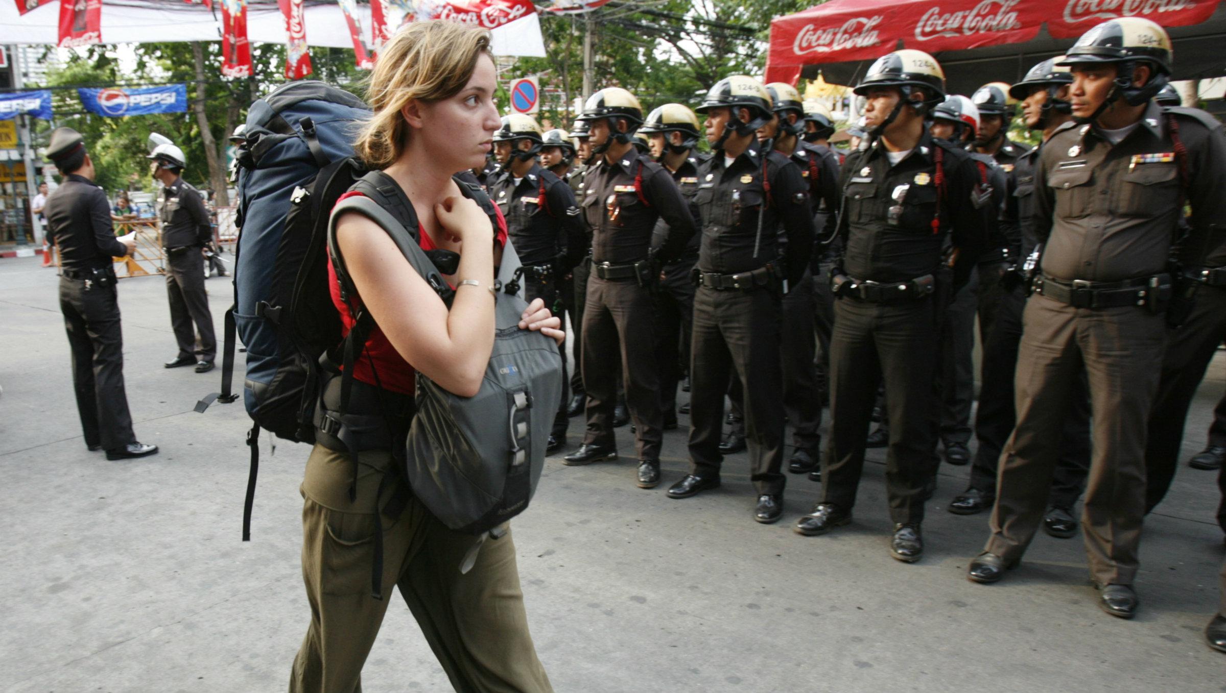 A tourist walks past policemen in Bangkok.