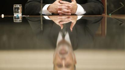 U.S. Federal Reserve Chairman Ben Bernanke is reflected in a glass table top as he holds town hall event for teachers at the Federal Reserve Board's building in Washington November 13, 2013.
