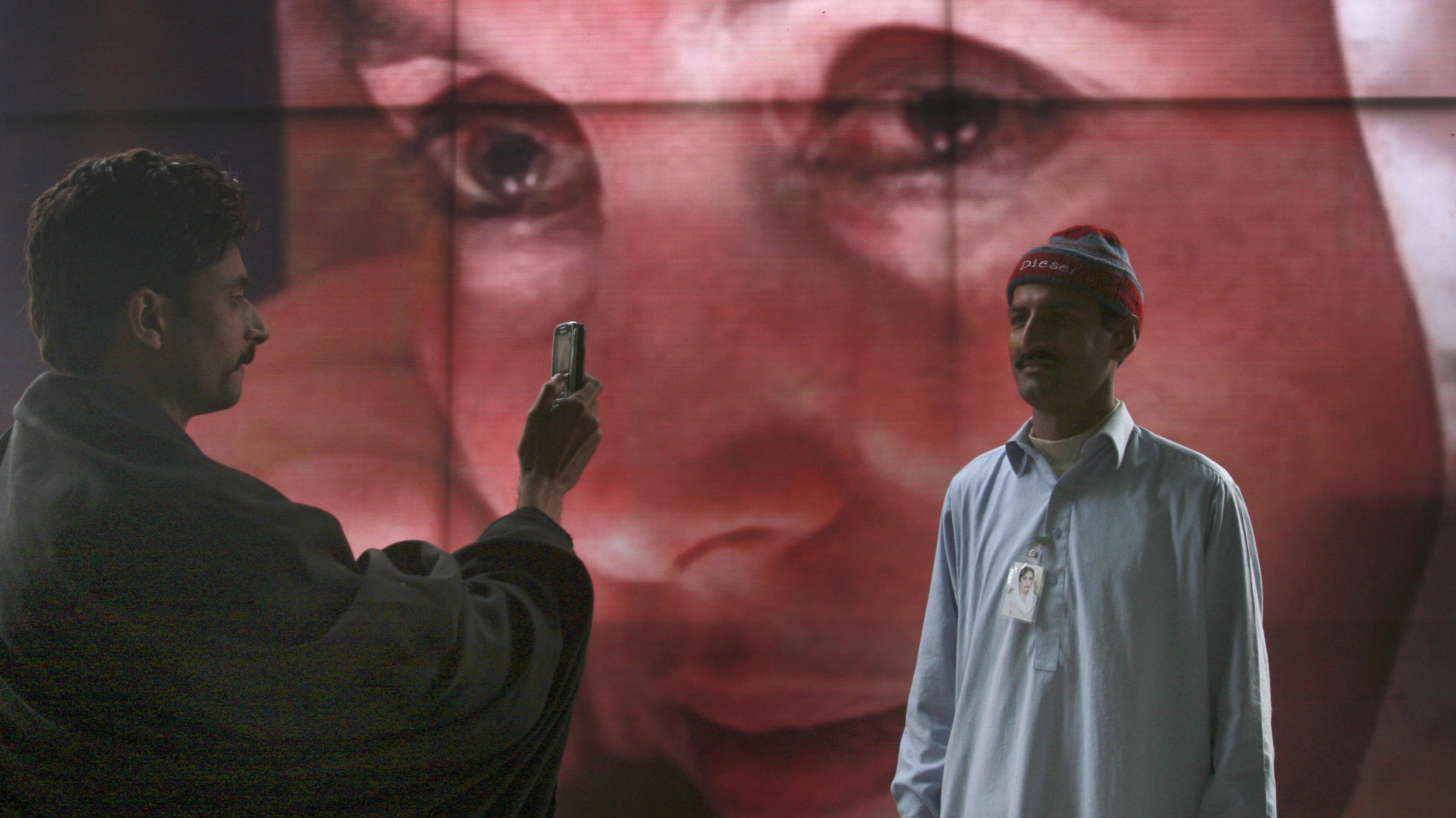 A man uses his mobile phone to take picture of his colleague in front of the poster of Pakistan's slain former Prime Minister Benazir Bhutto at her mausoleum, Saturday, Dec. 27, 2008 in Garhi Khuda Bakhsh near Larkana, Pakistan. Up to 200,000 Pakistanis gathered at the mausoleum of Bhutto on the first anniversary of her assassination, some of them walking hundreds of miles (kilometers) to get there. (AP Photo/Shakil Adil)
