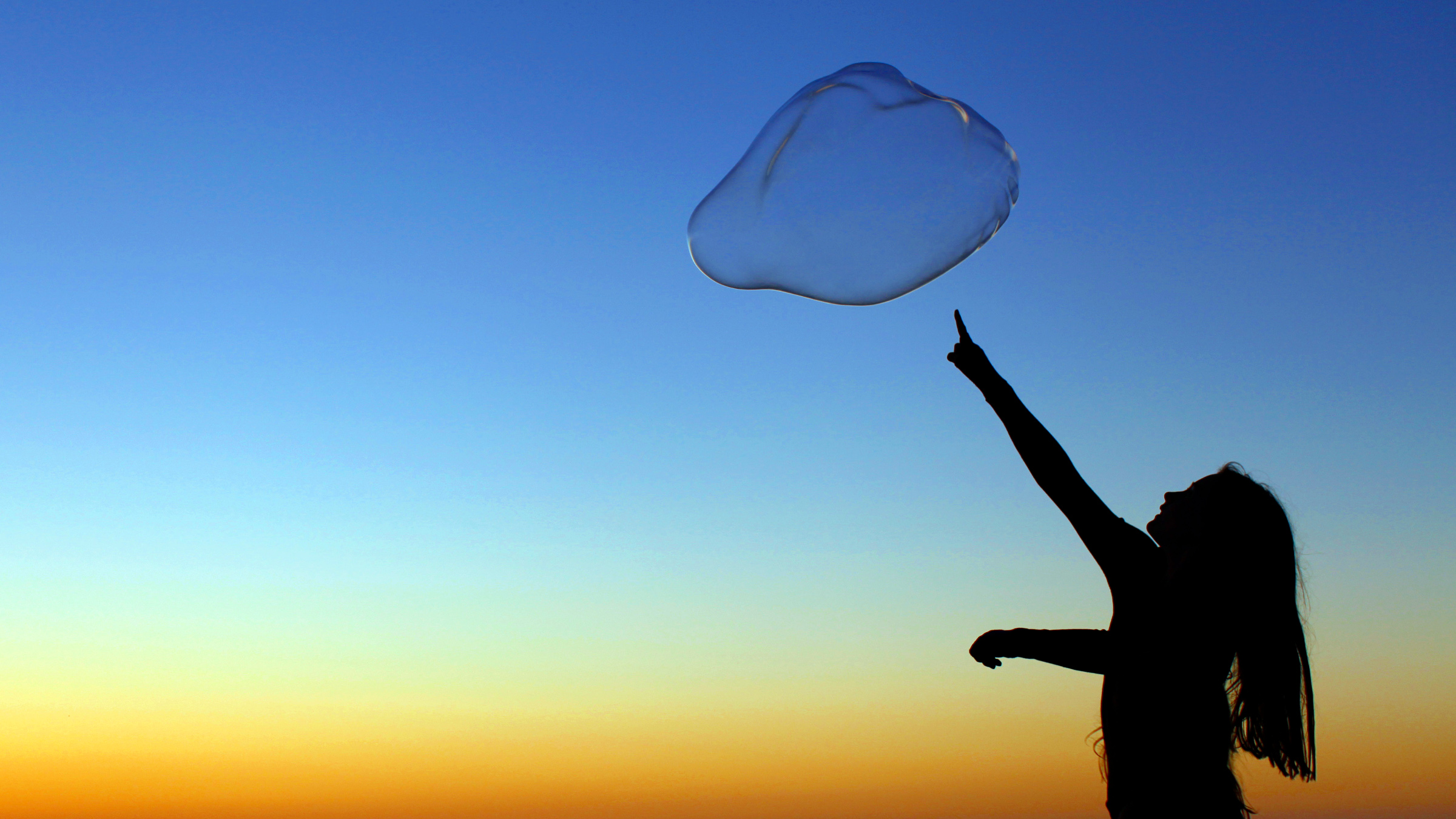 A girl plays with a giant bubble as the sun sets at Moonlight Beach in Encinitas, California June 30, 2011. Picture taken June 30.
