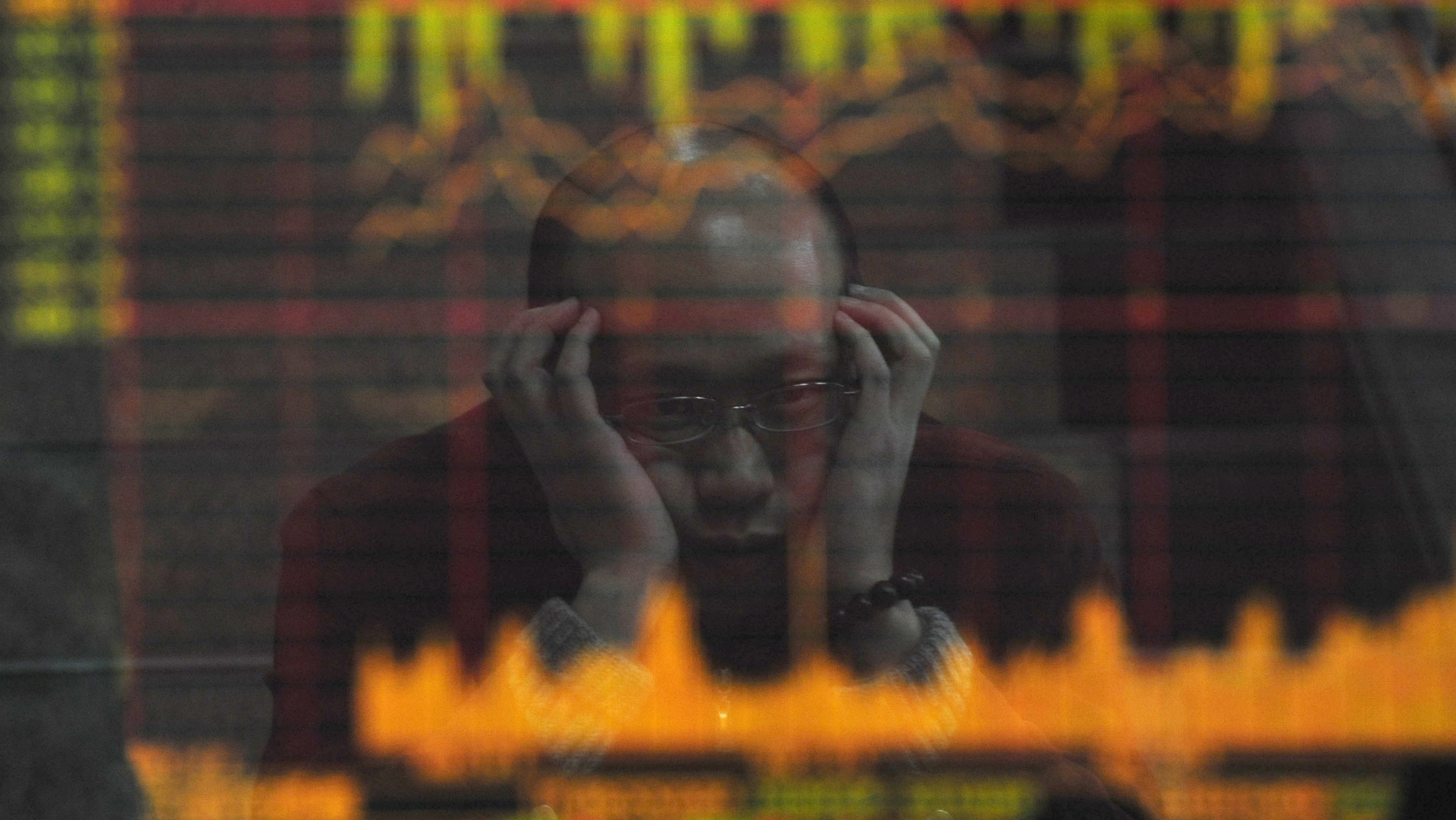An investor is reflected in a screen showing stock information at a brokerage house in Hefei, Anhui province February 18, 2009. China's stock market tumbled for a second straight day on Wednesday, and turnover shrank, because of fears that a surge in January bank lending could prove negative for the economy rather than signalling a recovery. REUTERS/Stringer