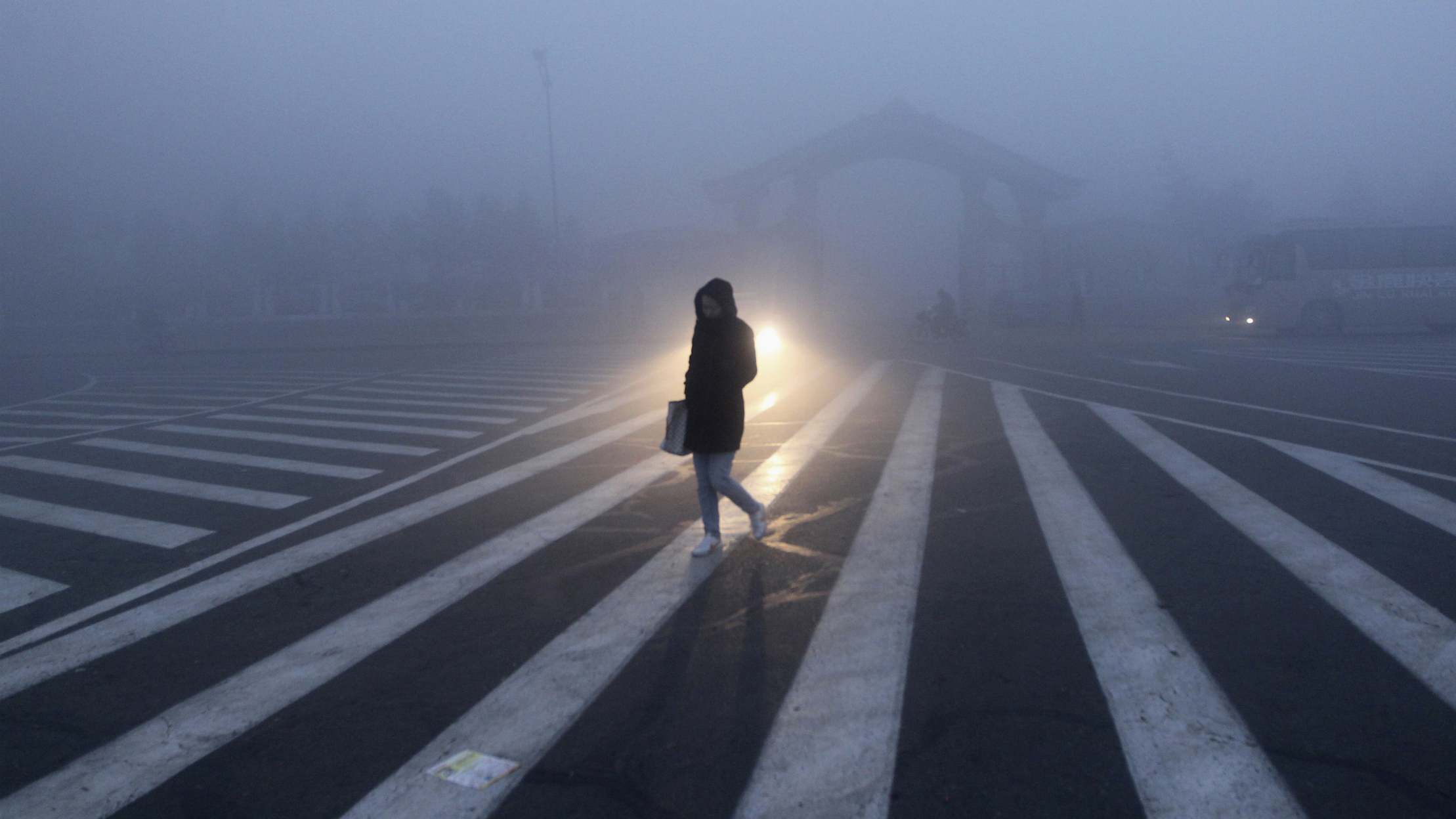 A woman walks along a street during a smoggy day in Changchun, Jilin province, October 22, 2013. The severe smog continued to shroud major cities in north-east China including Changchun, with its average visibility less than 5 metres (16 feet) at 6 am Tuesday, according to local media. REUTERS/China Daily