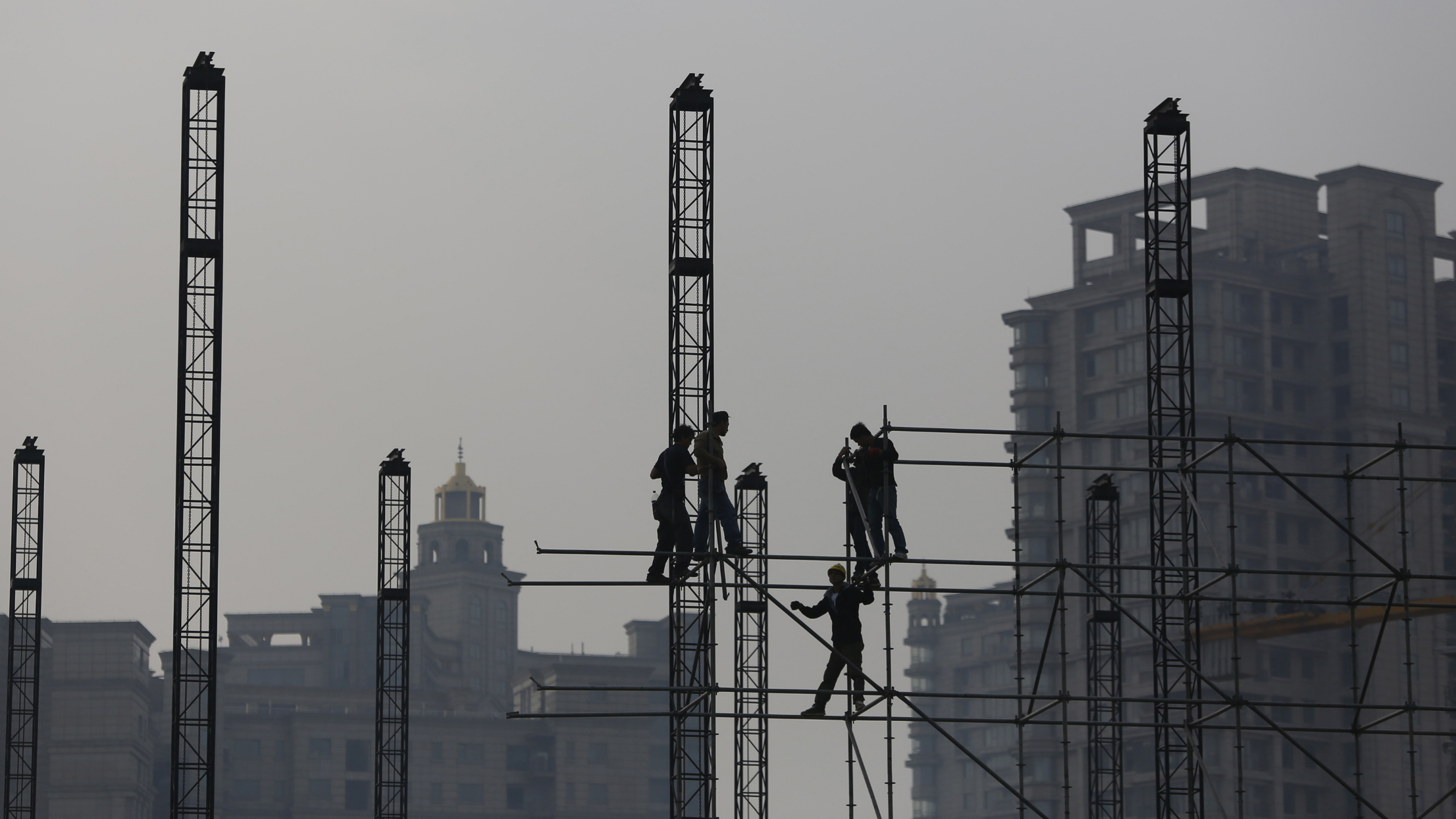 Workers install scaffolding at a construction site in front of residential buildings during a hazy day in Shanghai November 6, 2013. REUTERS/Aly Song