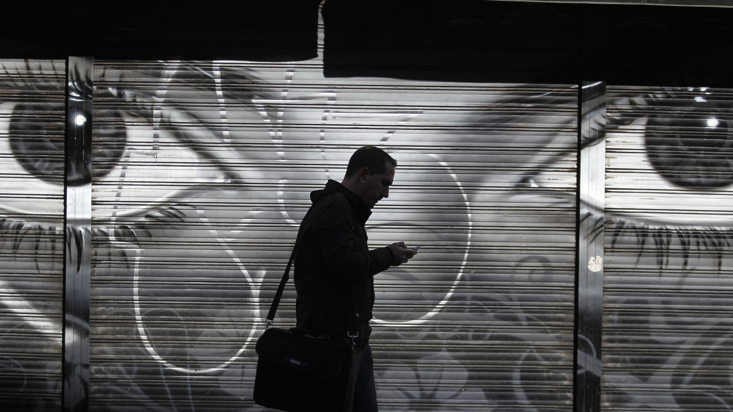"""A man looks at his cell phone as he walks on the street in downtown Madrid, Thursday, Oct. 31, 2013. On Wednesday Spain's Prime Minister Mariano Rajoy said that the head of Spain's intelligence services will address Parliament over allegations that Spain was a target for surveillance by the U.S. National Security Agency. He reiterated that if confirmed, such activity is """"inappropriate and unacceptable between partners and friends."""" (AP Photo/Francisco Seco)"""