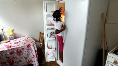"""Tashawna Green's daughter Taishaun, 6, reaches into the freezer for an ice pop at her home in Queens Village, New York August 21, 2011. Green who up until recently worked 25 hours a week at Target, is on food stamps and says a good number of her colleagues are too. Green made $8.08 cents an hour working for Target. """"It's a good thing that the government helps, but if employers paid enough and gave enough hours, then we wouldn't need to be on food stamps."""""""