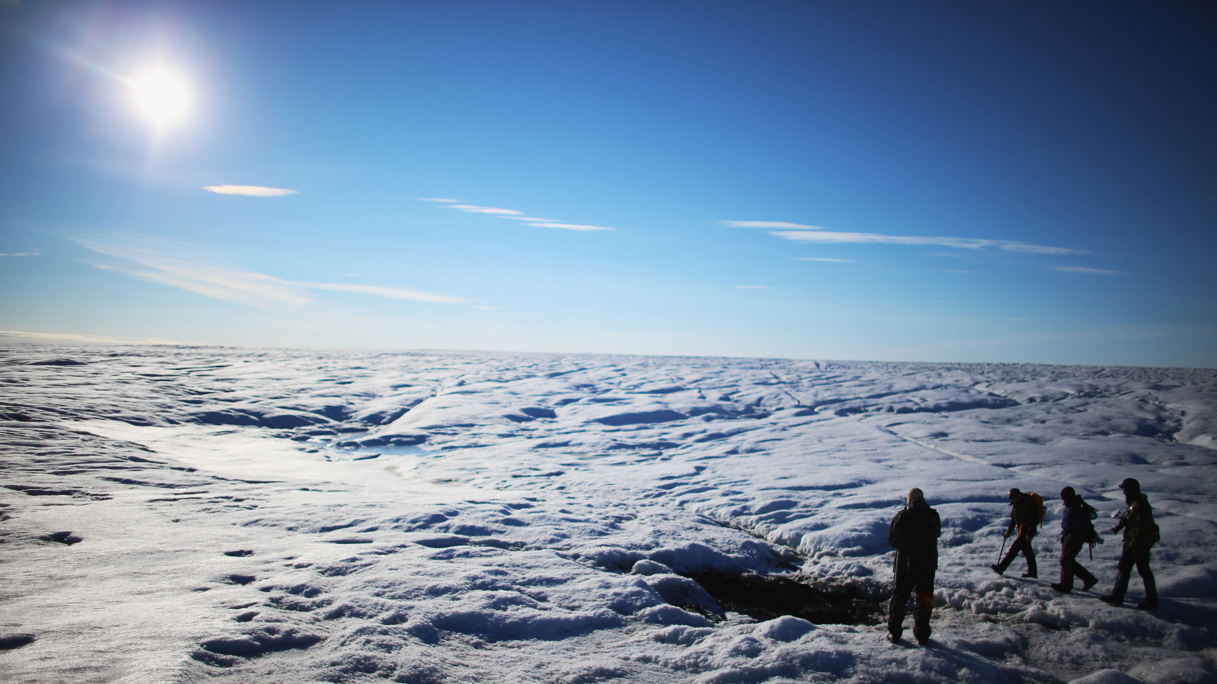 Scientists from the Woods Hole Oceanographic Institution and University of Washington walk across the glacier on July 15, 2013 on the Glacial Ice Sheet, Greenland.