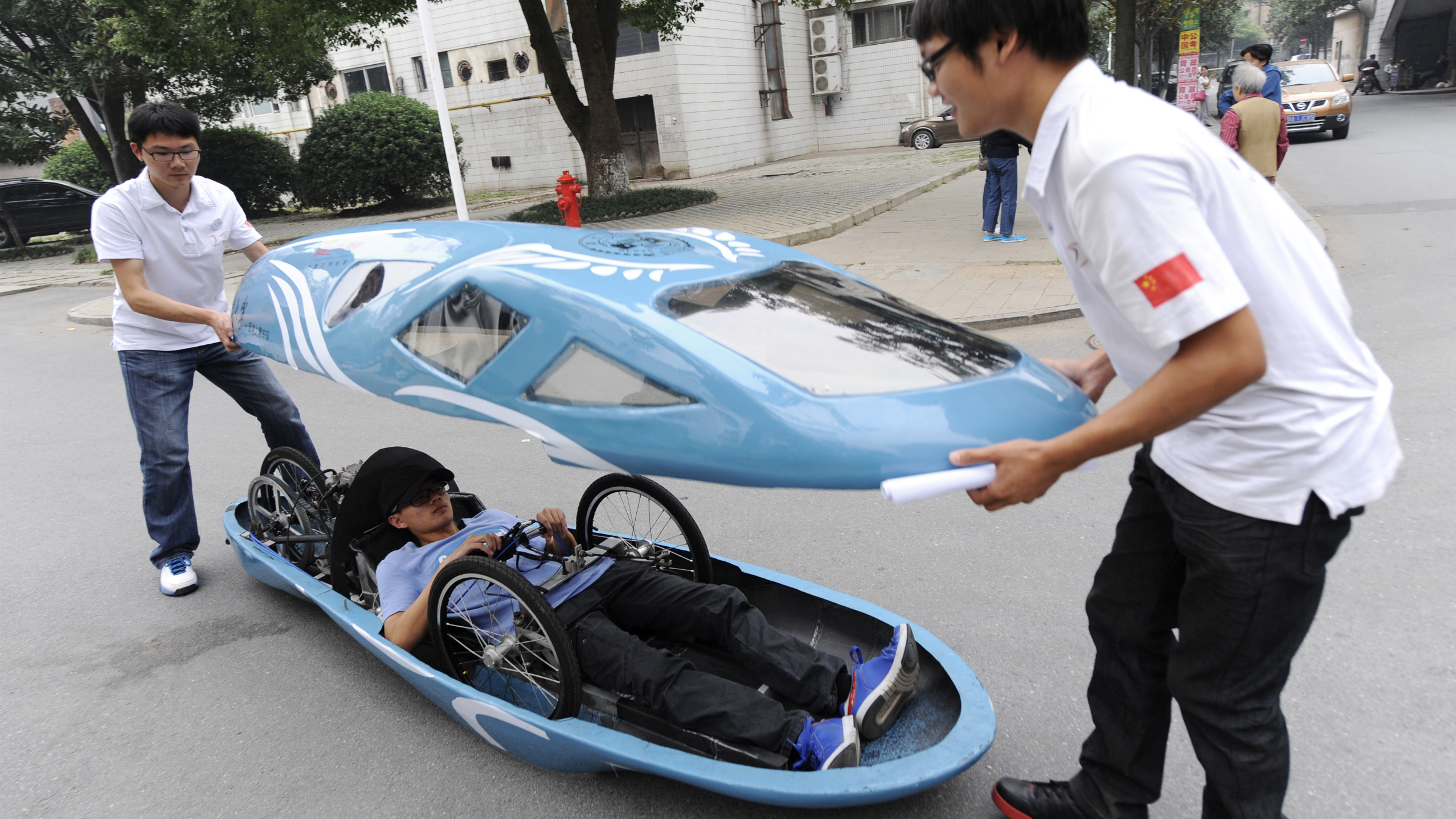 DATE IMPORTED:October 9, 2013Students open the top of a newly-made fuel-efficient vehicle on a street inside Hunan University after a test drive in Changsha, Hunan province October 8, 2013. A group of students at Hunan University designed and made the 2.85-metre-long innovative vehicle, which travels up to a maximum speed of 60km/h (37m/h), in six months with the cost of about 50,000 yuan ($8,168). The fuel-efficient vehicle, which is about 50 kilogram (110 lb) in weight, is able to travel 100 kilometres (62 miles) with one litre of gasoline, according to local media. Picture taken October 8, 2013. REUTERS/Stringer