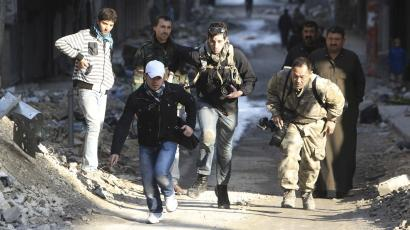 Journalists Bryn Karcha (C) of Canada and Toshifumi Fujimoto (R) of Japan run for cover next to an unidentified fixer in a street in Aleppo's district of Salaheddine December 29, 2012.