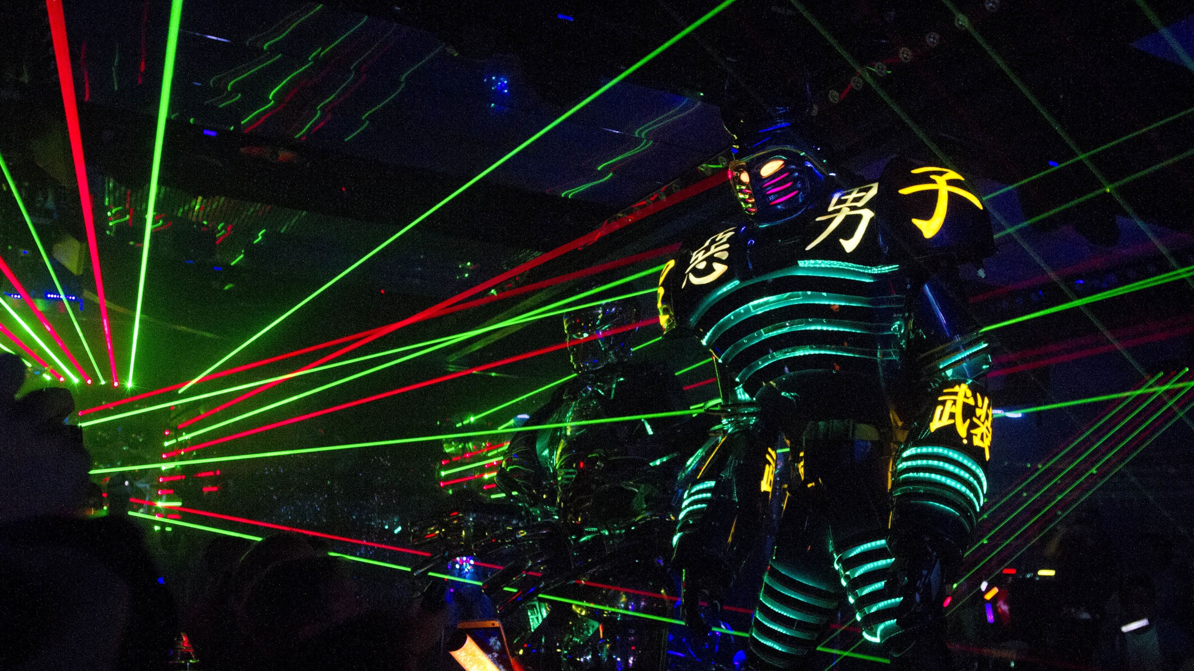 """Laser lights outline a robot during a performance at Robot Restaurant in Tokyo on Sunday October 6, 2013. Laser beams, robots, outlandish outfits, and flashing lights complete the otherworldly atmosphere of the cosplay, or """"costume play"""" themed restaurant. (AP Photo/Jacquelyn Martin)"""