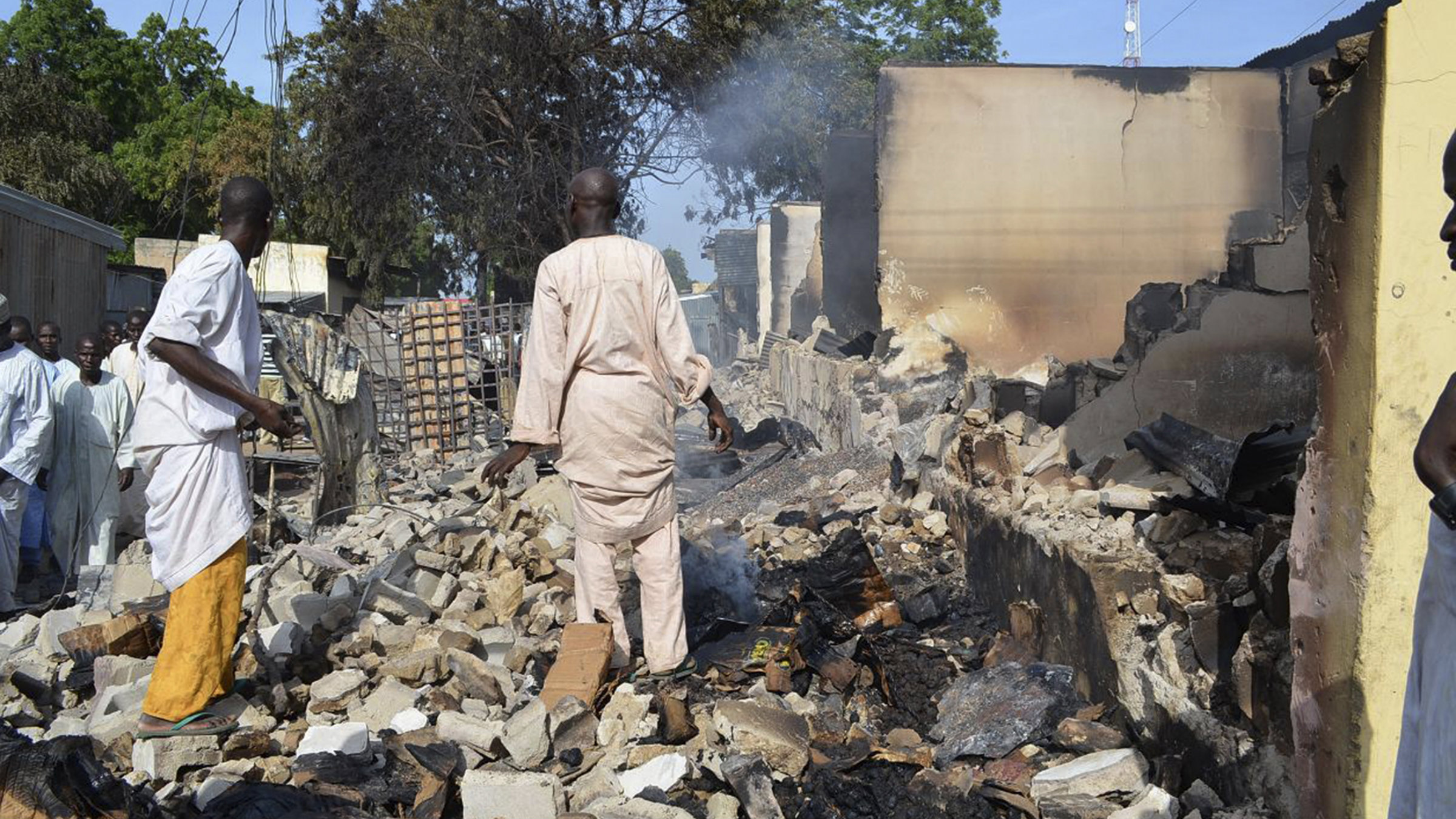Two men walk in the rubble after Boko Haram militants raided the town of Benisheik.