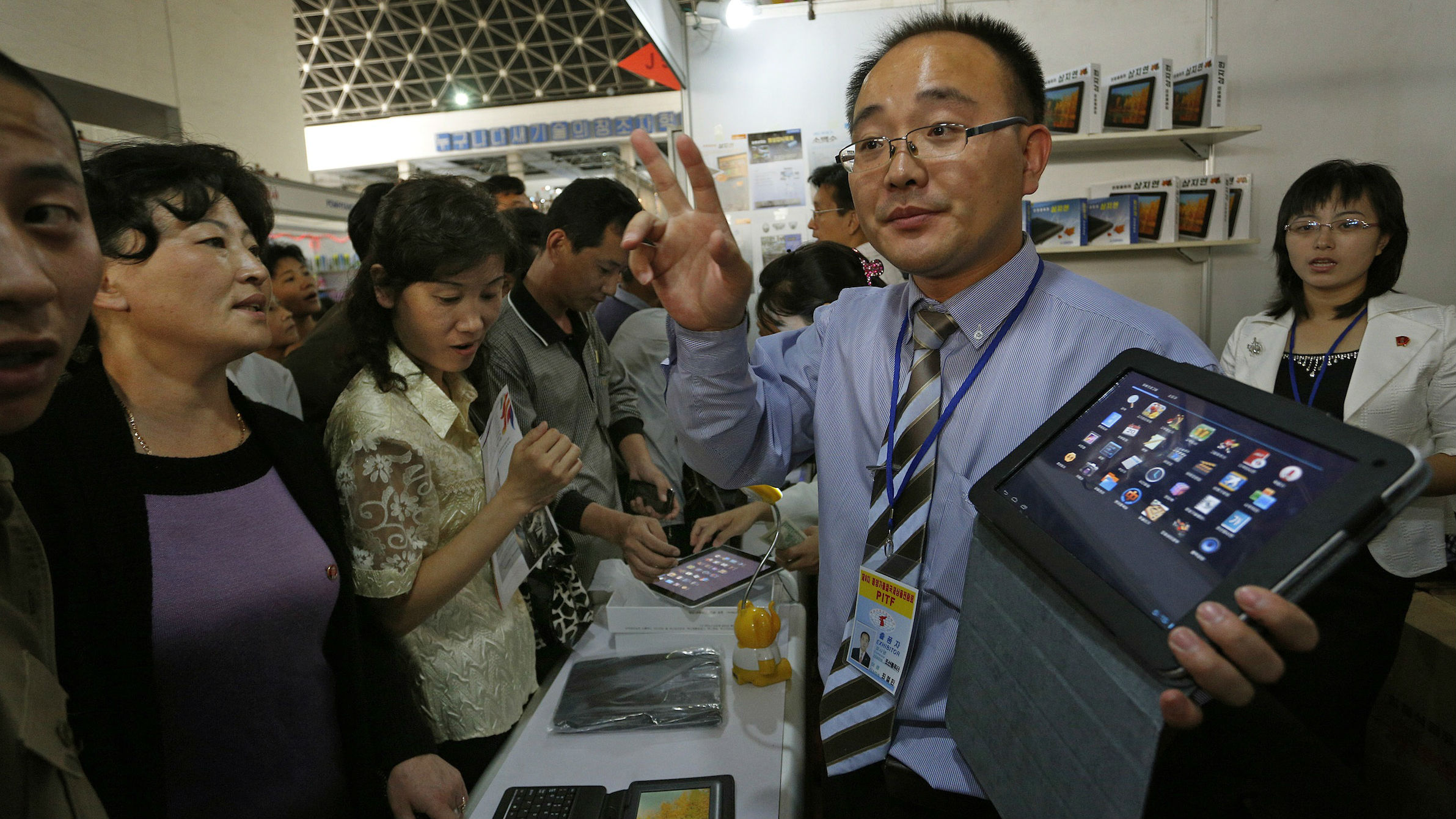 North Koreans looks at a new tablet product made by North Korea at a trade fair at the Three Revolution Exhibition Hall in Pyongyang Tuesday, Sept. 25, 2012.