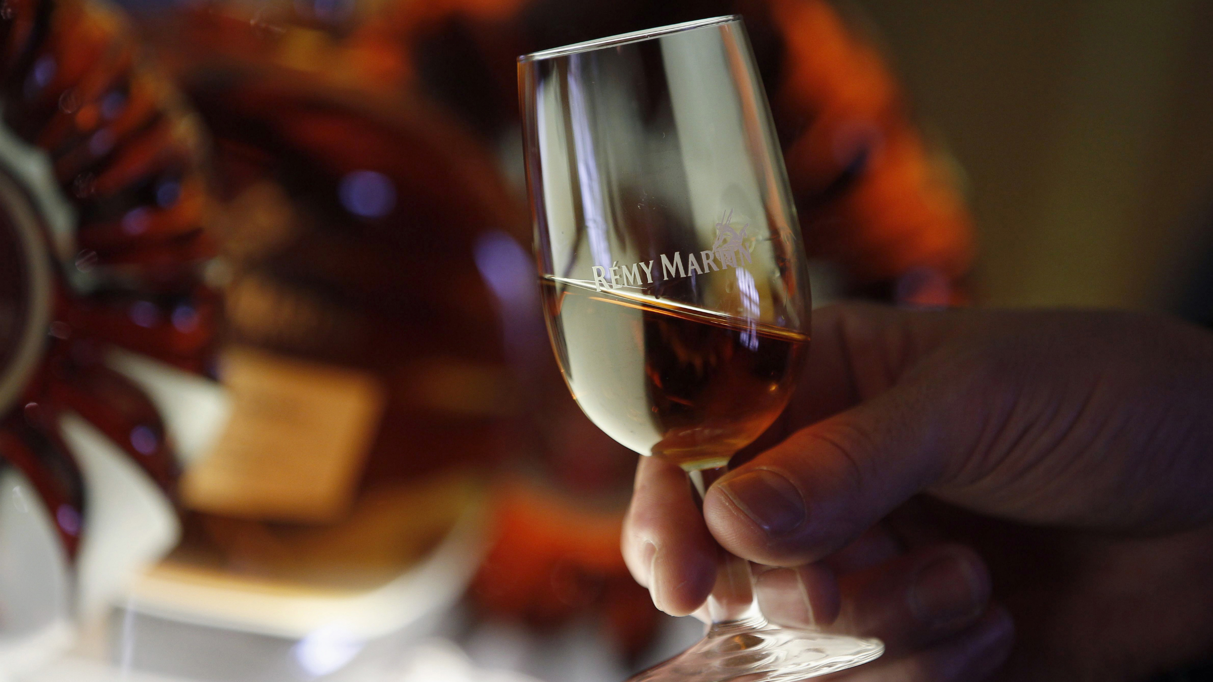 An employee holds a glass of cognac at the Remy Martin distillery in Cognac, southwestern France, October 8, 2012. As overall cognac sales have recovered from the 2008/09 downturn, discerning Chinese looking for an aspirational tipple are causing a surge in shipments of Remy Martin's 2,500-euro Louis XIII cognac and other deluxe spirits. The trend is good news for Remy Martin, which is much more focused than its rivals on high-end brands, and suggests that a slowdown in China's overall economic growth rate may not dampen the country's appetite for some luxury goods, even if some sectors have sounded warnings. To match Feature COGNAC-REMY/ Picture taken October 8, 2012. REUTERS/Regis Duvignau