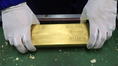 An employee holds an ingot of gold at the precious metals safe vault of the Central Bank in Moscow January 24, 2011. REUTERS/Sergei Karpukhin