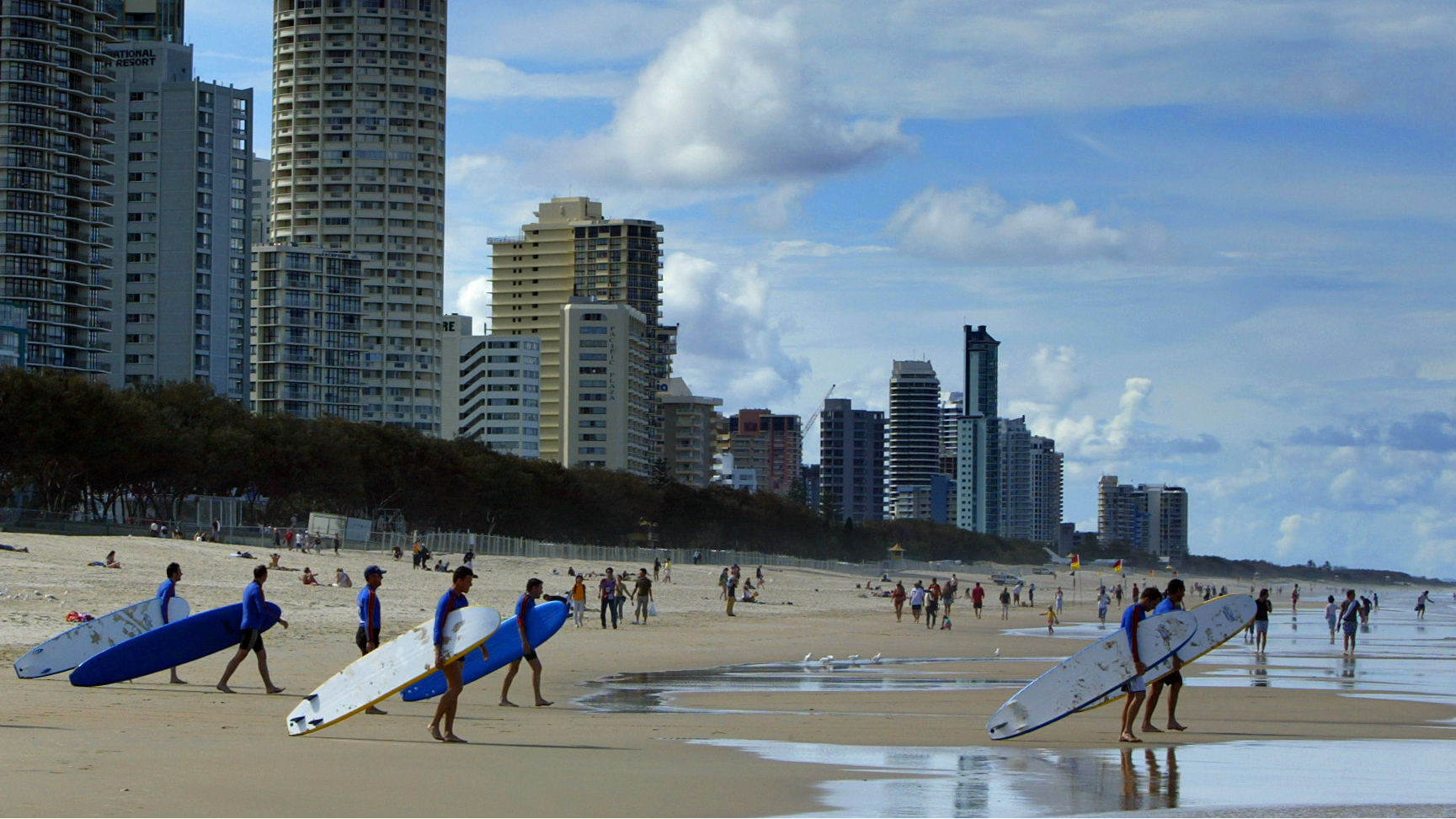 ongboard surfers from a surf school walk into the water at the popular tourist destination of Main Beach at Surfer's Paradise, 60 kilometres southeast of Brisbane, October 17, 2003. The Australian Tourism Commission managing director Ken Boundy said today that the launch of a Qantas low cost domestic airline next year to rival Richard Branson's carrier Virgin Blue would give both domestic and international travellers an advantage, adding that it will encourage foreign visitors to get out beyond the cities. REUTERS/David Gray