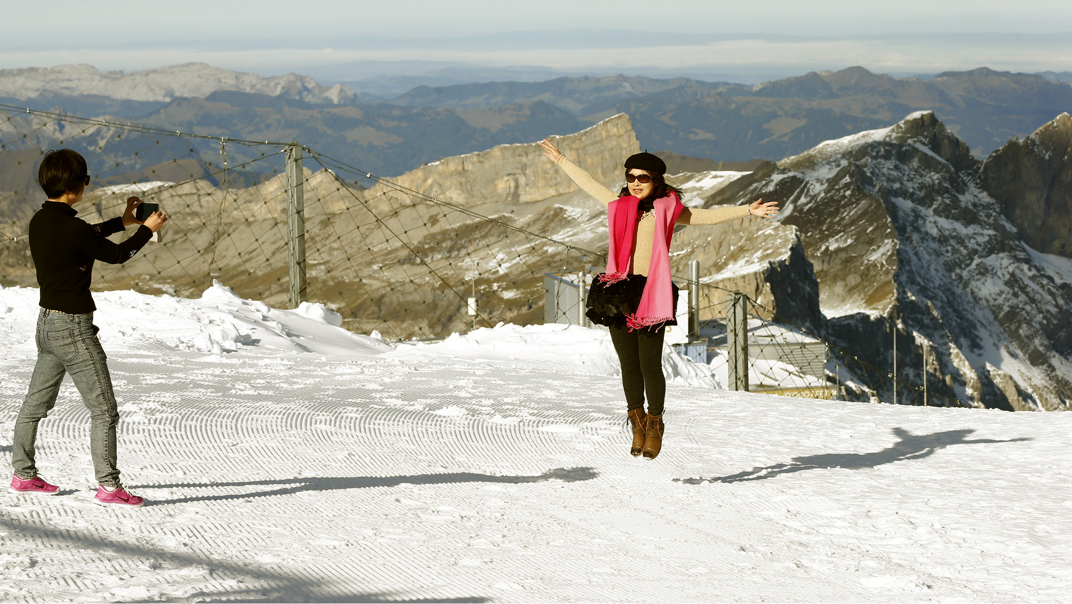 A tourist from China jumps up as she poses for a photograph at the Mount Titlis skiing area (3,238 m/10,623 ft) near the Swiss mountain resort of Engelberg October 19, 2013. REUTERS/Arnd Wiegmann