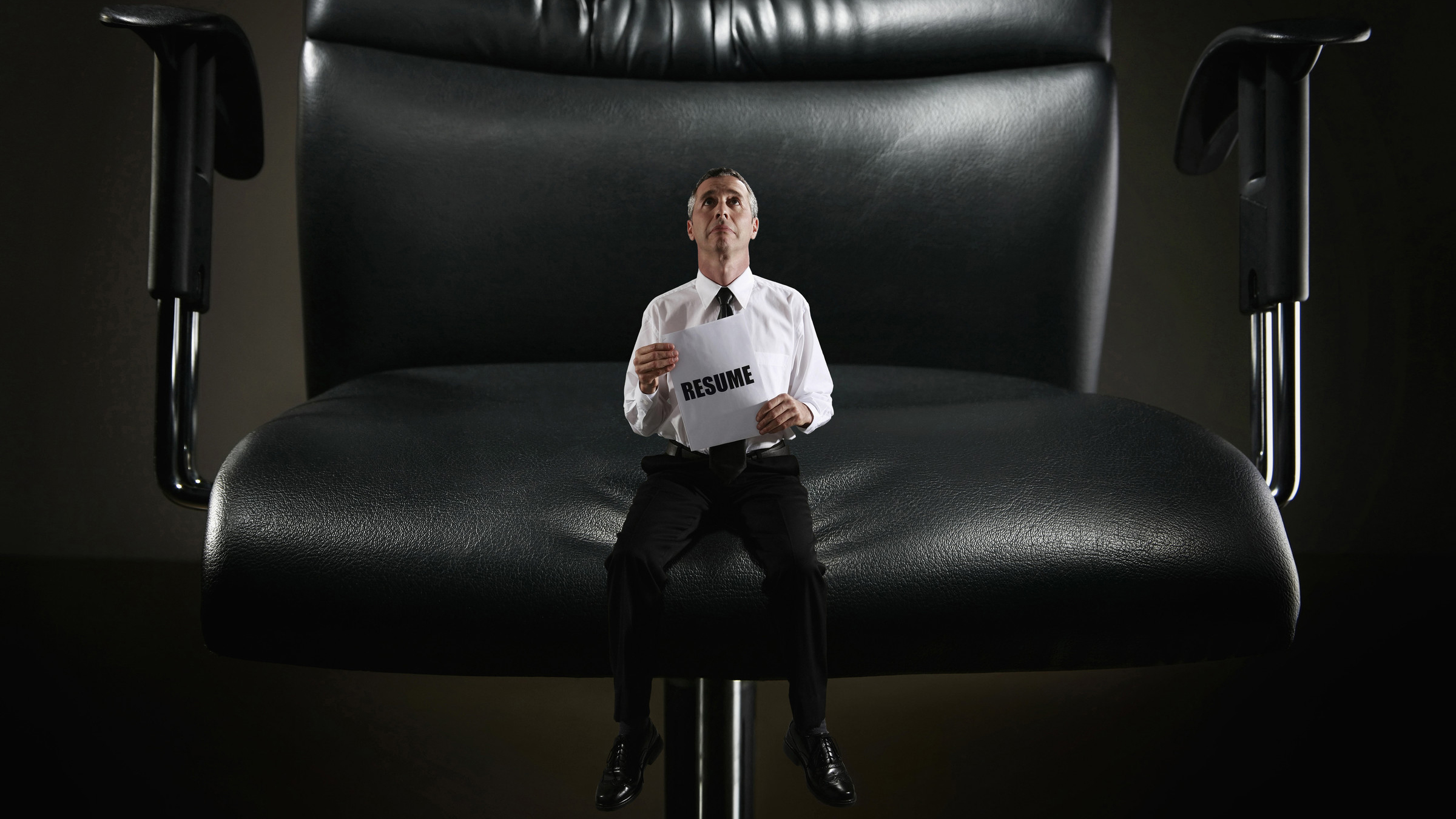 Mini Sized Businessman Sitting on a Giant Chair Holding Resume --- Image by © Inspirestock/Corbis