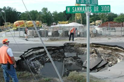 Plant City, Fla. workers look into a sinkhole that developed early Monday, May 29, 2000, in Plant City, Fla. (AP Photo/Dale Wilson