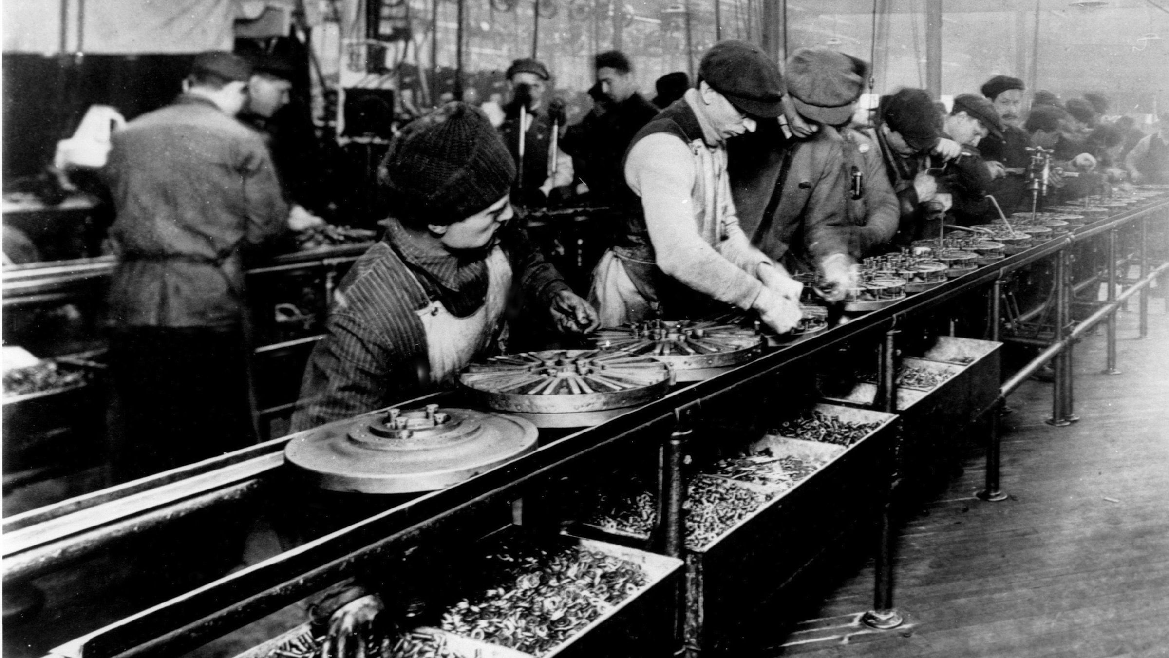 Workers are photographed on a flywheel assembly line at the Ford Motor Company's Highland Park, Mi., plant in 1913.  The use of a moving line reduced a car's assembly time from 12 hours to 93 minutes. The world's first automatic conveyor belt escalated the Industrial Age inspiring Henry Ford toward an unprecedented $5 per day minimum wage and an eight-hour day when auto industry workers were making $2.34 for a  nine-hour shift. Faster assemblage meant quicker availability, giving impetus to America's car culture and an ever-increasing mobile society.  (AP Photo/Ford Motor Company)