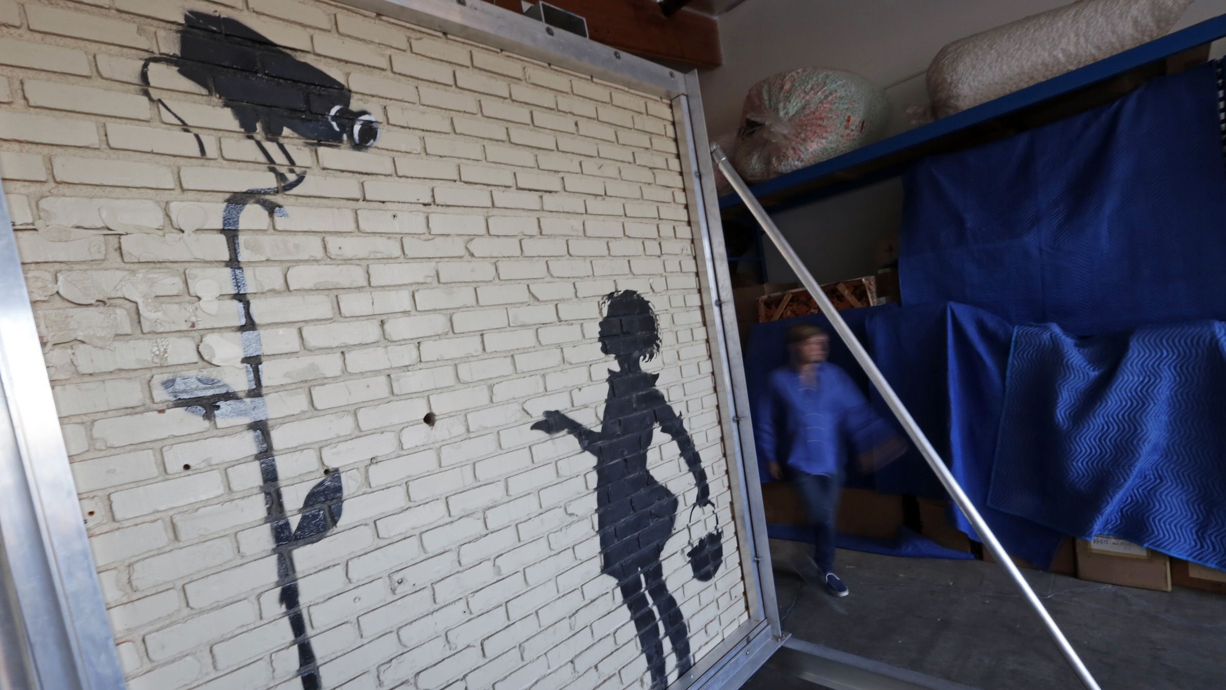 """Michael Doyle, street art director for Julien's Auctions, walks near """"Flower Girl,"""" a delicate stencil on a massive brick wall by popular street artist Banksy, that is displayed in a warehouse in the greater Los Angeles area Wednesday, Dec. 4, 2013. The artist painted it on the side of a Los Angeles gas station in 2008. The building's owner carefully removed the wall section, which is 9 feet high, 8 feet wide and weighs nearly 5,000 pounds, framed it in sturdy aluminum and brought it to Julien's Auctions.  Doyle says the piece could fetch more than $300,000 at auction on Thursday, because, """"Celebrities are Banksy-crazy."""" (AP Photo/Reed Saxon)"""