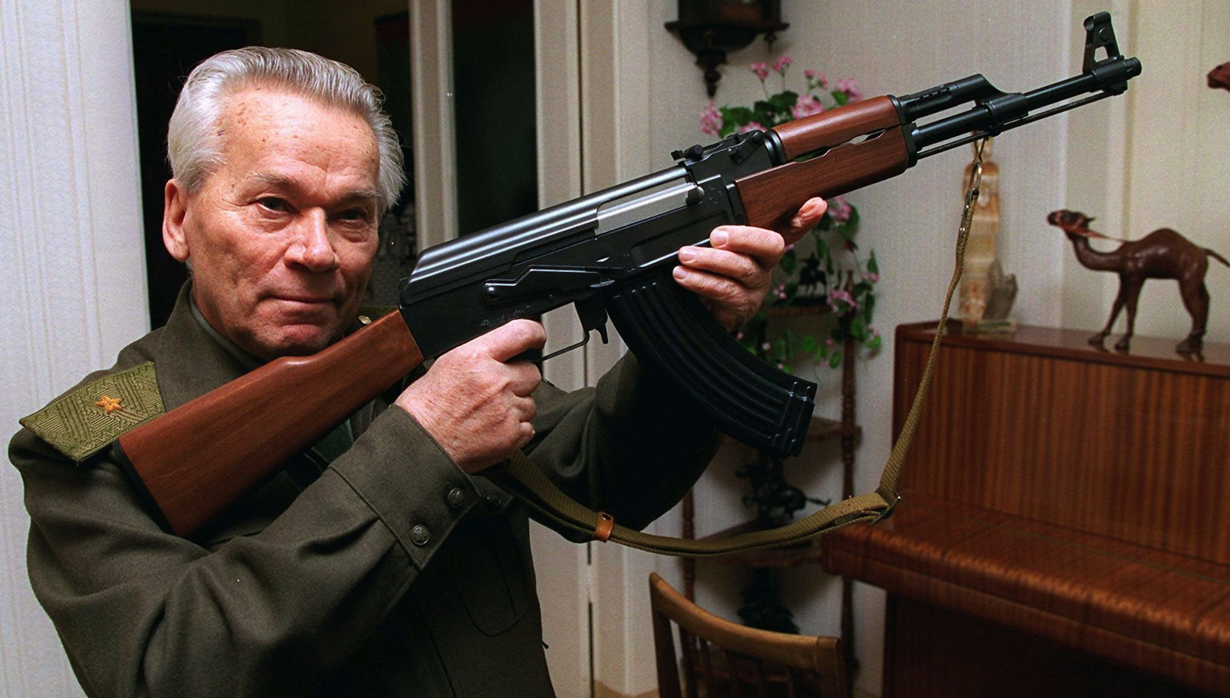 FILE- In this Wednesday, Oct. 29, 1997 file photo Mikhail Kalashnikov shows a model of his world-famous AK-47 assault rifle at home in the Ural Mountain city of Izhevsk, 1000 km (625 miles) east of Moscow, Russia. Kalashnikov, whose work as a weapons designer for the Soviet Union is immortalized in the name of the world's most popular firearm, died Monday at the age of 94 in a hospital of the city of Izhevsk where he lived. The AK-47 has been favored by guerrillas, terrorists and the soldiers of many armies. An estimated 100 million guns are spread worldwide.  (AP Photo/Vladimir Vyatkin, File)
