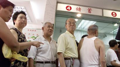 Chinese depositors queue to withdraw money at a bank in China's financial capital of Shanghai September 10, 2002. The service culture at China's state banks, legacy of a socialist-style planned economy in which their major role was to channel household savings into a creaky industrial sector. With over half of corporate loans having gone bad and customer-savvy foreign banks setting up shop, China's banks need to start rolling out service fast to wean themselves off interest income, tidy balance sheets and diversify risk, analysts said. REUTERS/Claro Cortes