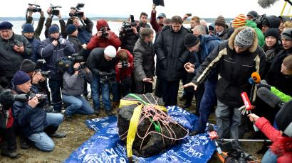 An object (C), which is a piece of a meteorite according to local authorities and scientists, is on display on the bank of the Chebarkul Lake, after it was lifted from the bottom of the lake, some 80 kilometers (50 miles) west of Chelyabinsk October 16, 2013. The meteorite exploded over central Russia in February 2013, raining fireballs over a vast area and causing a shock wave that smashed windows, damaged buildings and injured more than 1,000 people, according to local media.