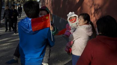 Visitors to the forbidden city, carry children holding the Chinese national flags in Beijing, China, Saturday, Nov. 16, 2013. Some 15 million to 20 million Chinese parents will be allowed to have a second baby after the Chinese government announced Friday, Nov. 15, 2013 that couples where one partner has no siblings can have two children, in the first significant easing of the country's strict one-child policy in nearly three decades. (AP Photo/Ng Han Guan
