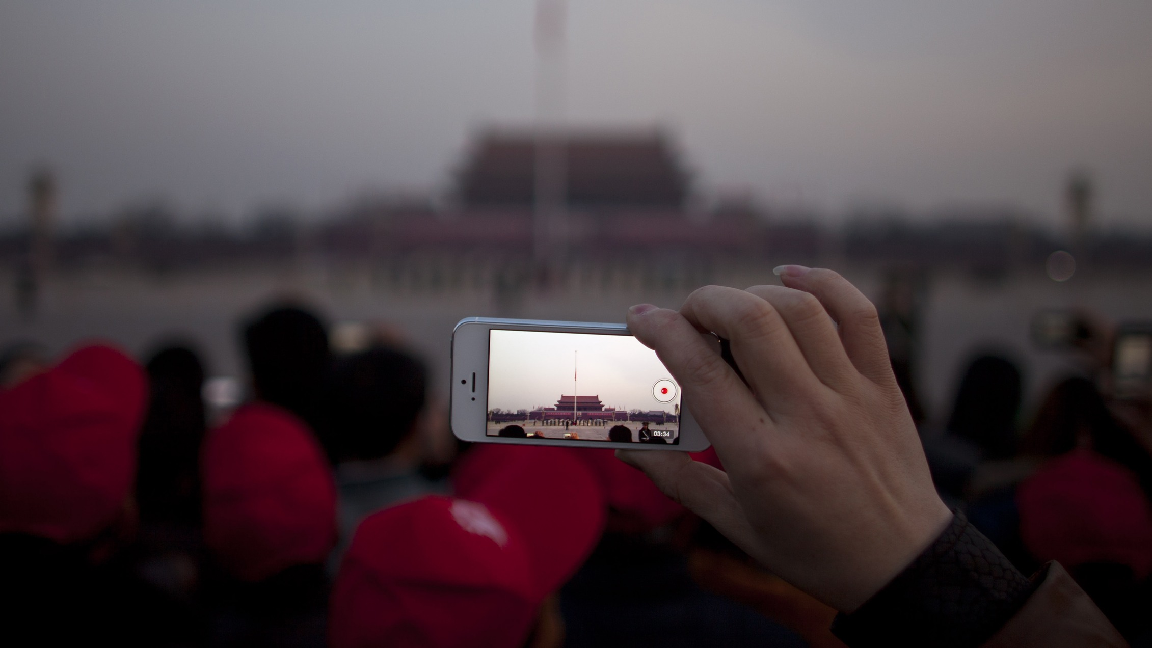 A Chinese tourist uses his smart phone to take videos of a flag raising ceremony on Tiananmen Square at dawn before the opening session of the annual National People's Congress held in the nearby Great Hall of the People, Beijing, China, Tuesday, March 5, 2013. China's government promised its people Tuesday deficit-fueled spending to fight deep-seated corruption, improve the despoiled environment and address other quality-of-life issues demanded by an increasingly vocal public looking for change. (AP Photo/Alexander F. Yuan)