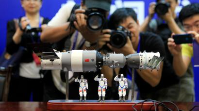 Photographers take pictures of a model of the Shenzhou-9 manned spacecraft ( R) docking with the orbiting Tiangong-1 space lab module (L) and three Chinese astronauts after a news conference at Jiuquan Satellite Launch Center, in northwest China's Gansu province, June 15, 2012. The Shenzhou-9 manned spacecraft will be launched at 18:37 (10:37 GMT) on June 16, 2012, according to a decision made by China's manned space docking program headquarters, Xinhua News Agency reported.