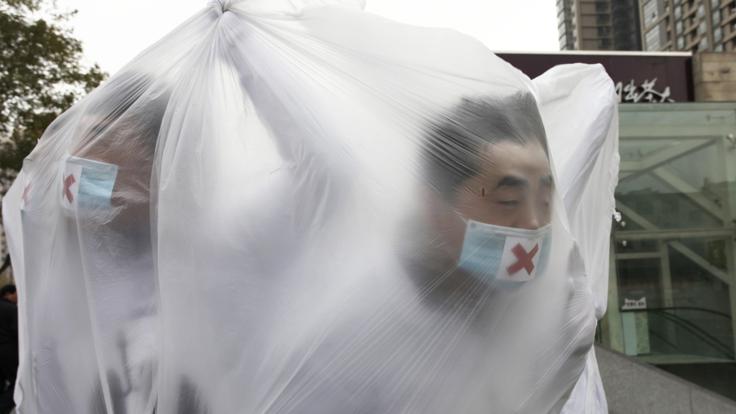 College students wearing masks cover themselves with plastic bags as they participate in a performance art to raise awareness of air pollution, in Xi'an, Shaanxi province December 5, 2013. China's stability-obsessed leadership has become increasingly concerned by the abysmal air quality in cities, as it plays into popular resentment over political privilege and rising inequality in the world's second-largest economy. REUTERS/Stringer