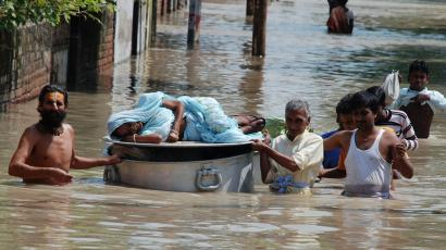 An ailing woman is carried on top of a cooking pot through flood waters after heavy monsoon rains in the northern Indian city of Vrindavan September 25, 2010. India's monsoon is likely to start receding by early October, the weather office said on Thursday, limiting the risk of crop damage from floods in the north that could be triggered if unusual heavy rains persist. REUTERS/K. K. Arora