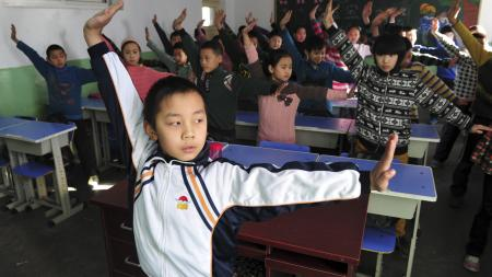 "Pupils practice a set of martial arts ""smog preventing"" exercises in a classroom at a primary school in Shijiazhuang, Hebei province December 11, 2013. The school invented the set of exercises, which consists of 23 different martial arts moves, claiming it can improve physical conditions of the students and reduce the harm of smog. Air quality in cities is of increasing concern to China's stability-obsessed leaders, anxious to douse potential unrest as a more affluent urban population turns against a growth-at-all-costs economic model that has poisoned much of the country's air, water and soil. Picture taken December 11, 2013. REUTERS/Stringer"